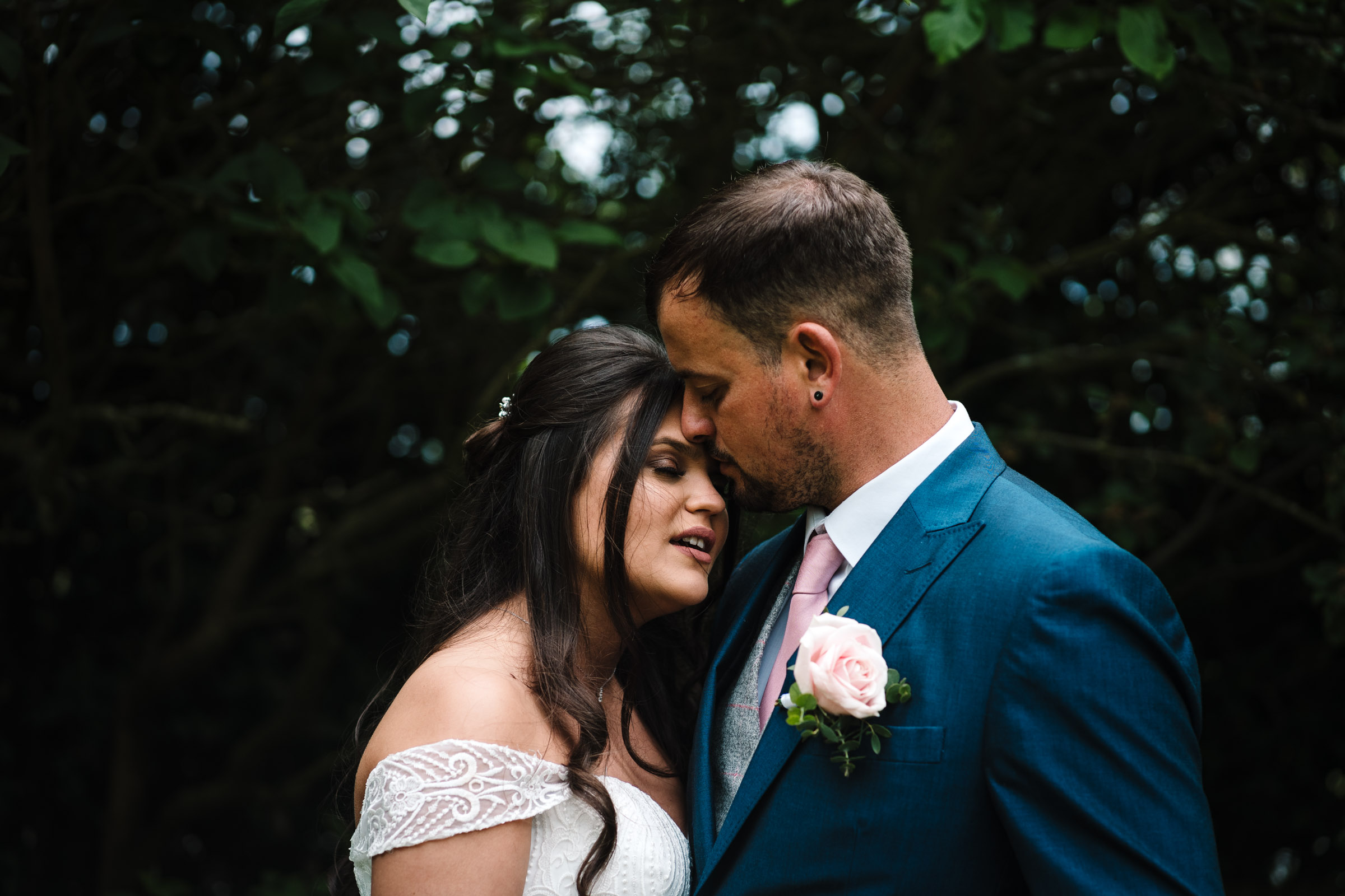 Bride and groom standing close, groom kissing brides forehead