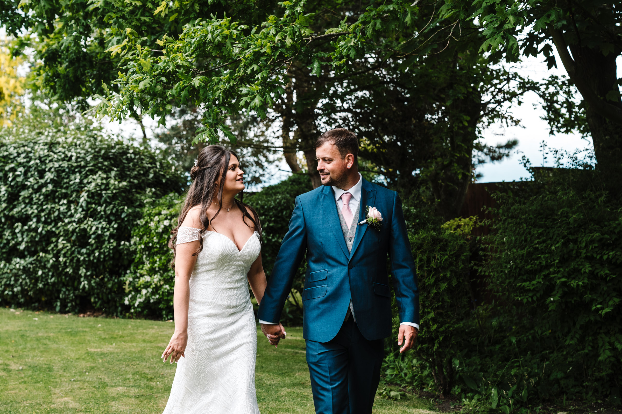 bride and groom walking in the garden at royal arms hotel