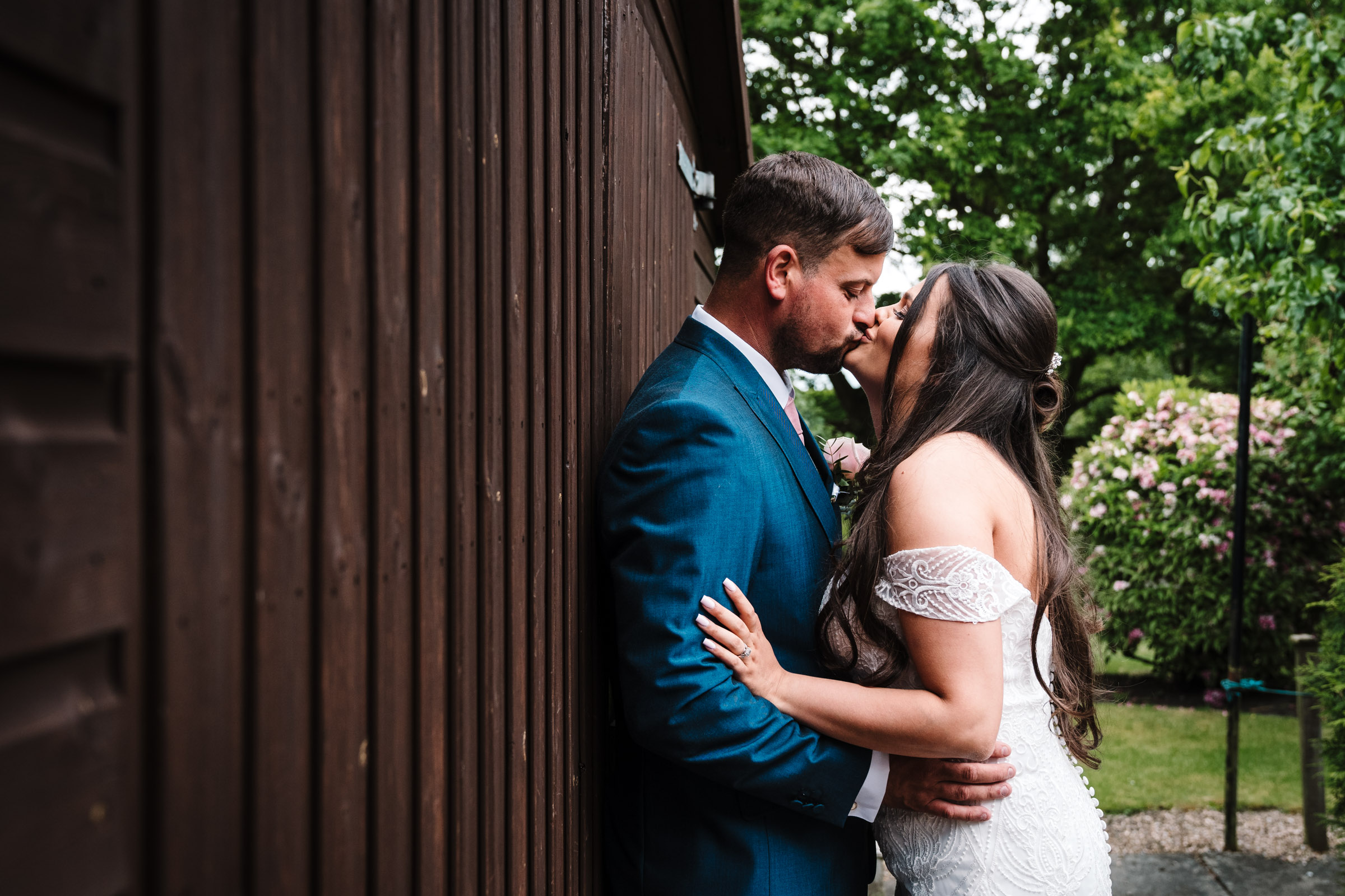 bride and groom kissing, standing against a shed at royal arms hotel