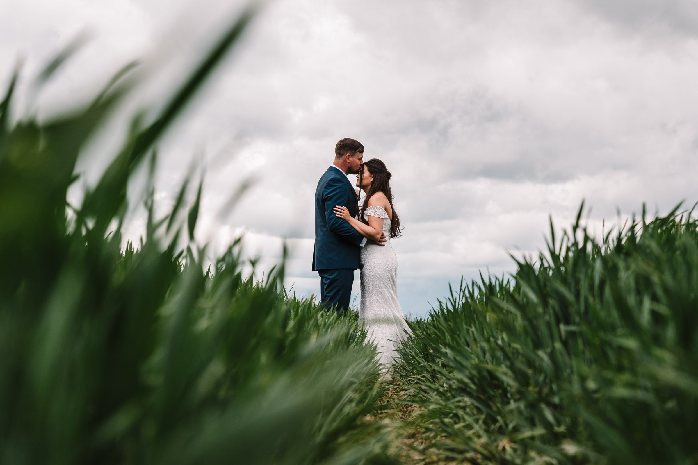 Bride and groom standing together in a field, royal arms hotel wedding
