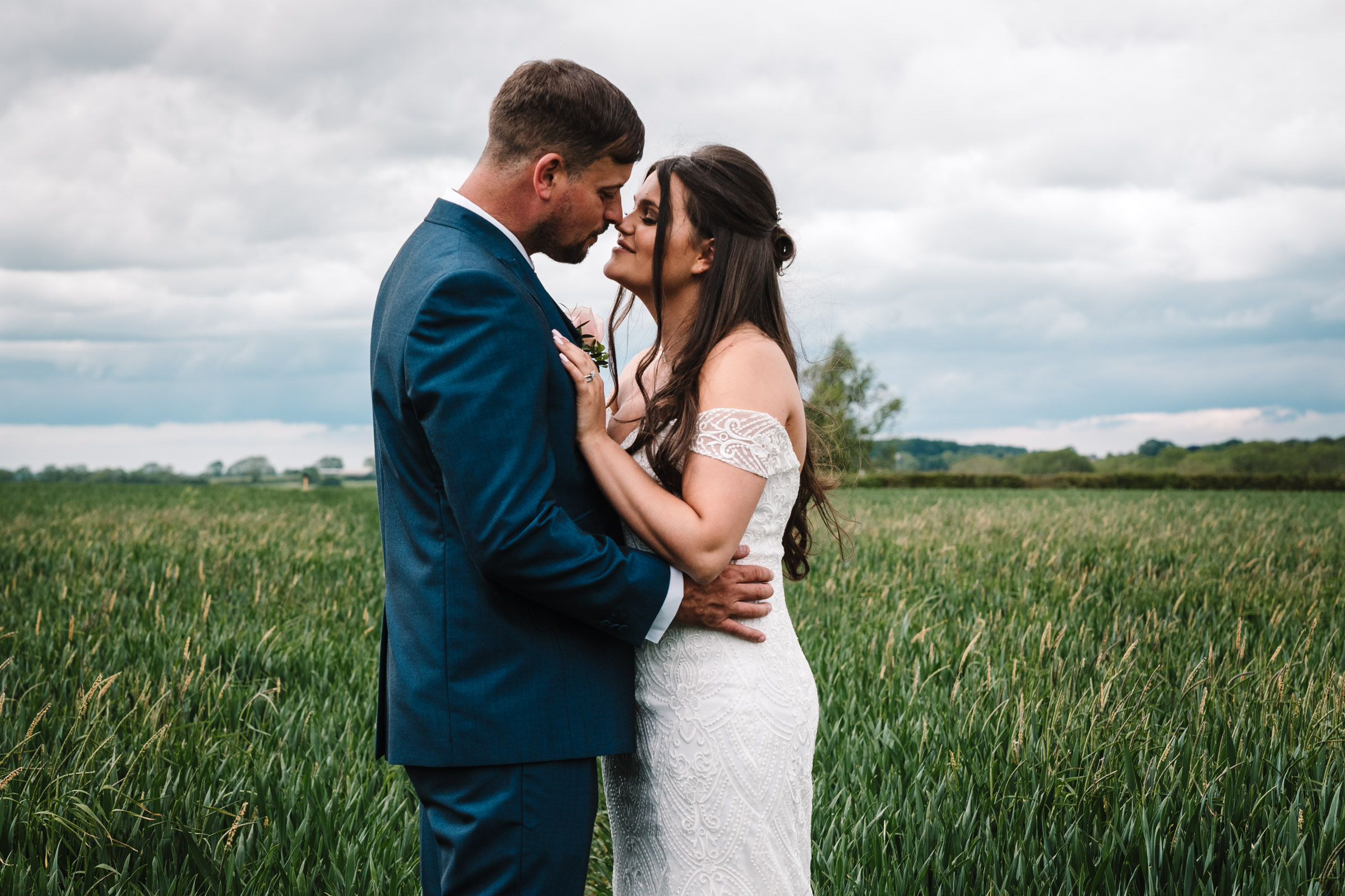 bride and groom holding each other close in field, royal arms hotel