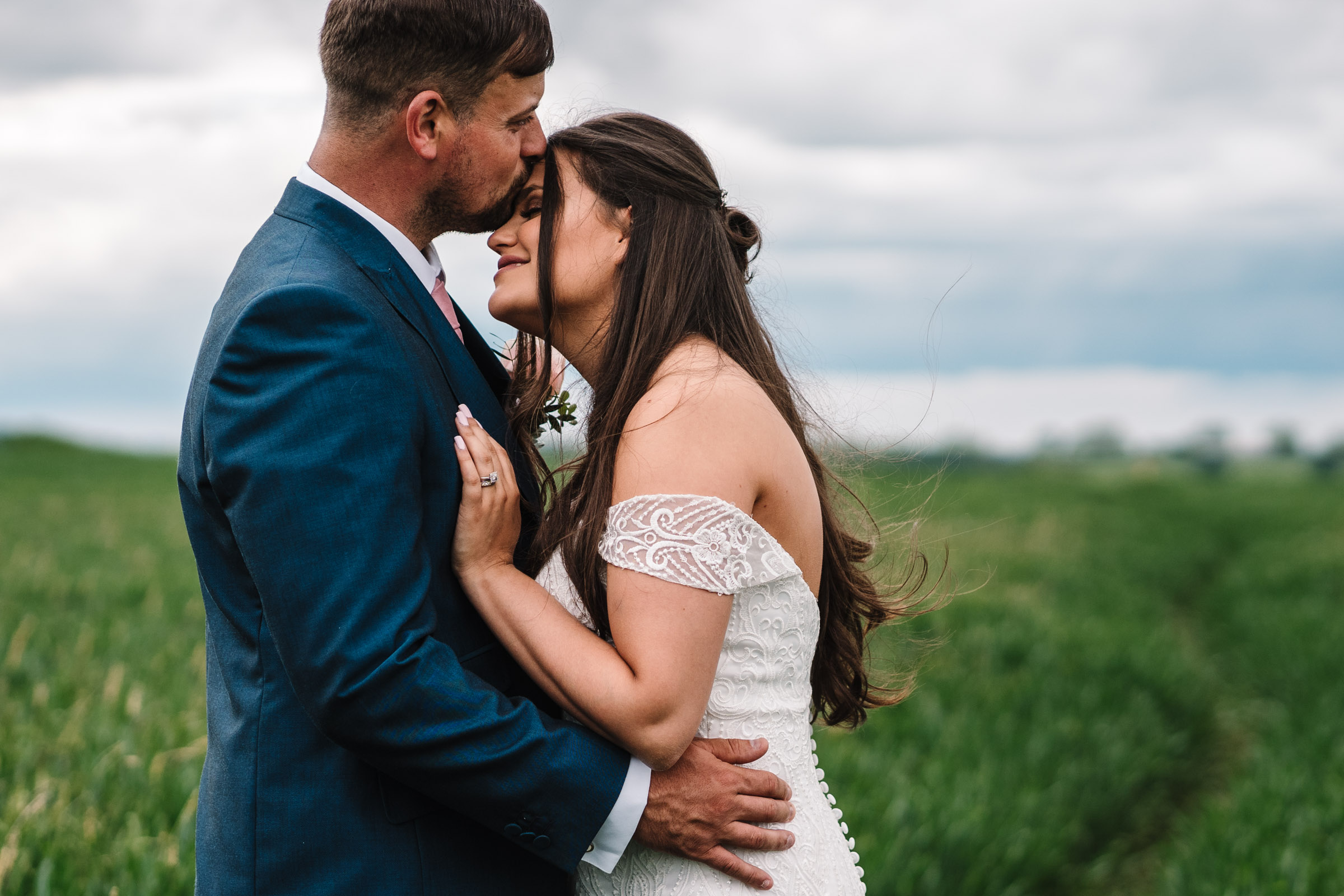 Groom kissing brides forehead, standing in a field
