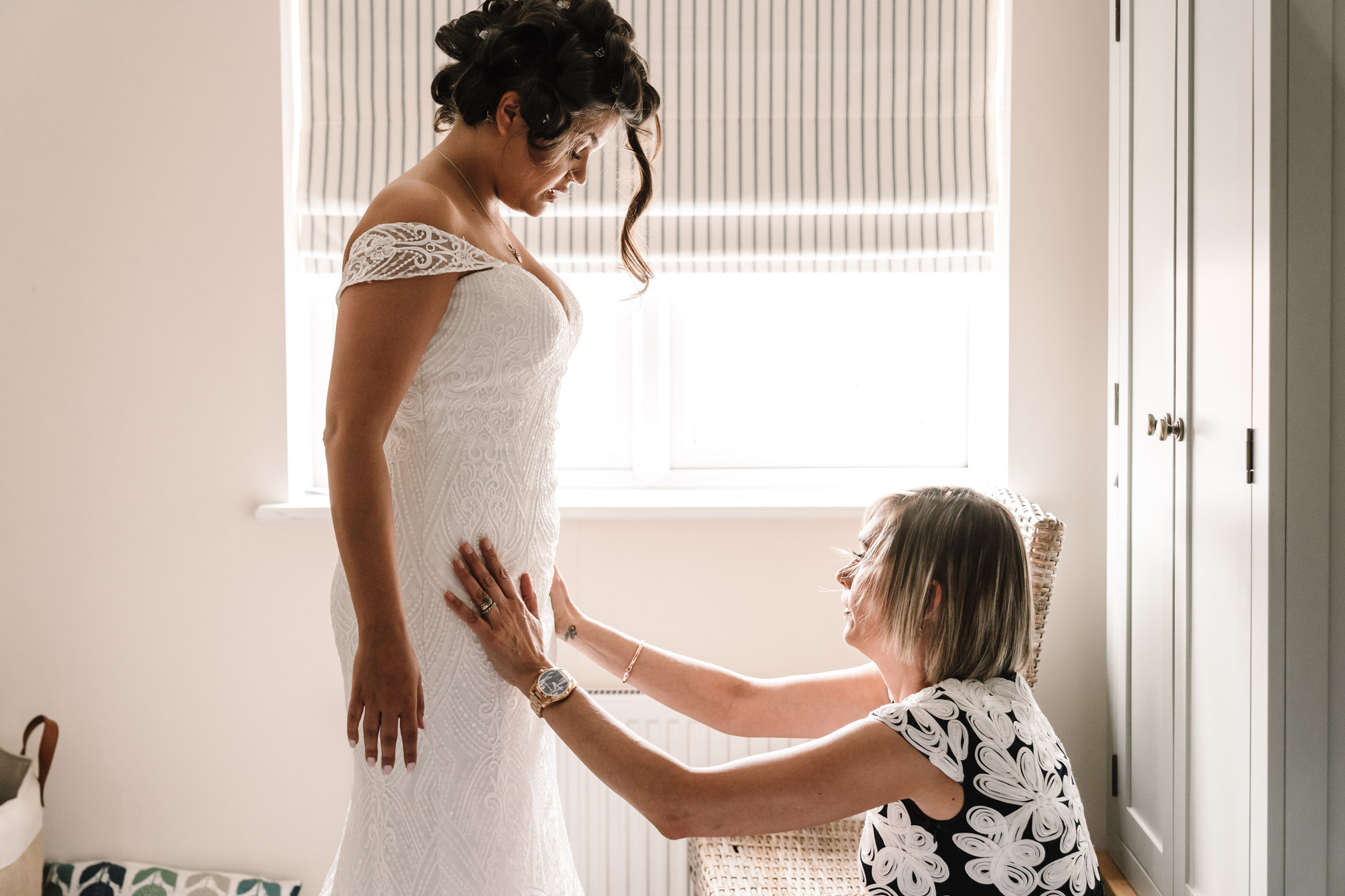 Bride getting into her wedding dress with her Mum