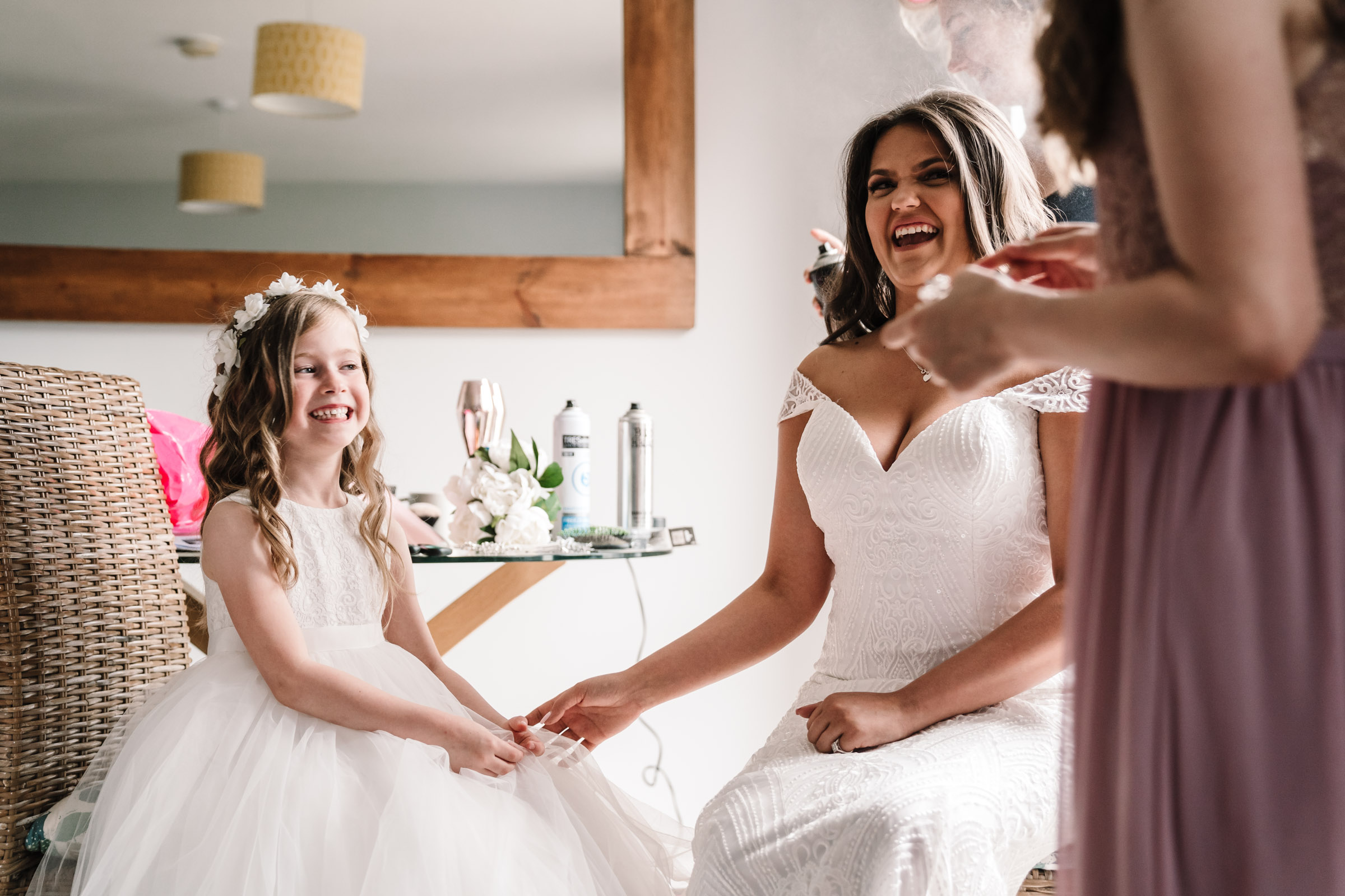 bride laughing with flower girl, bridal prep