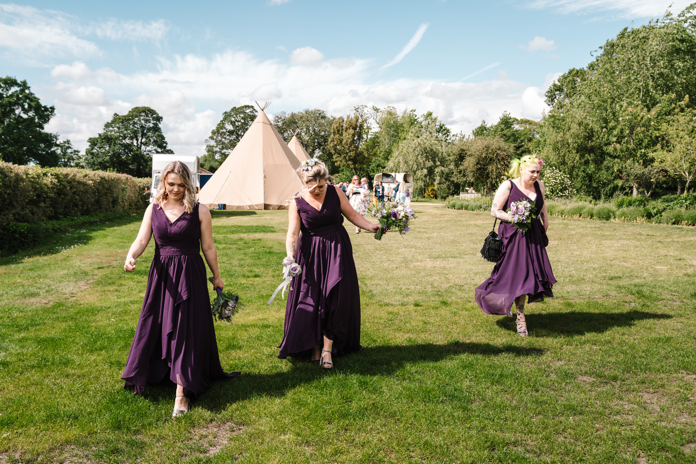 bridesmaids walking across lawn at castle bromwich hall gardens