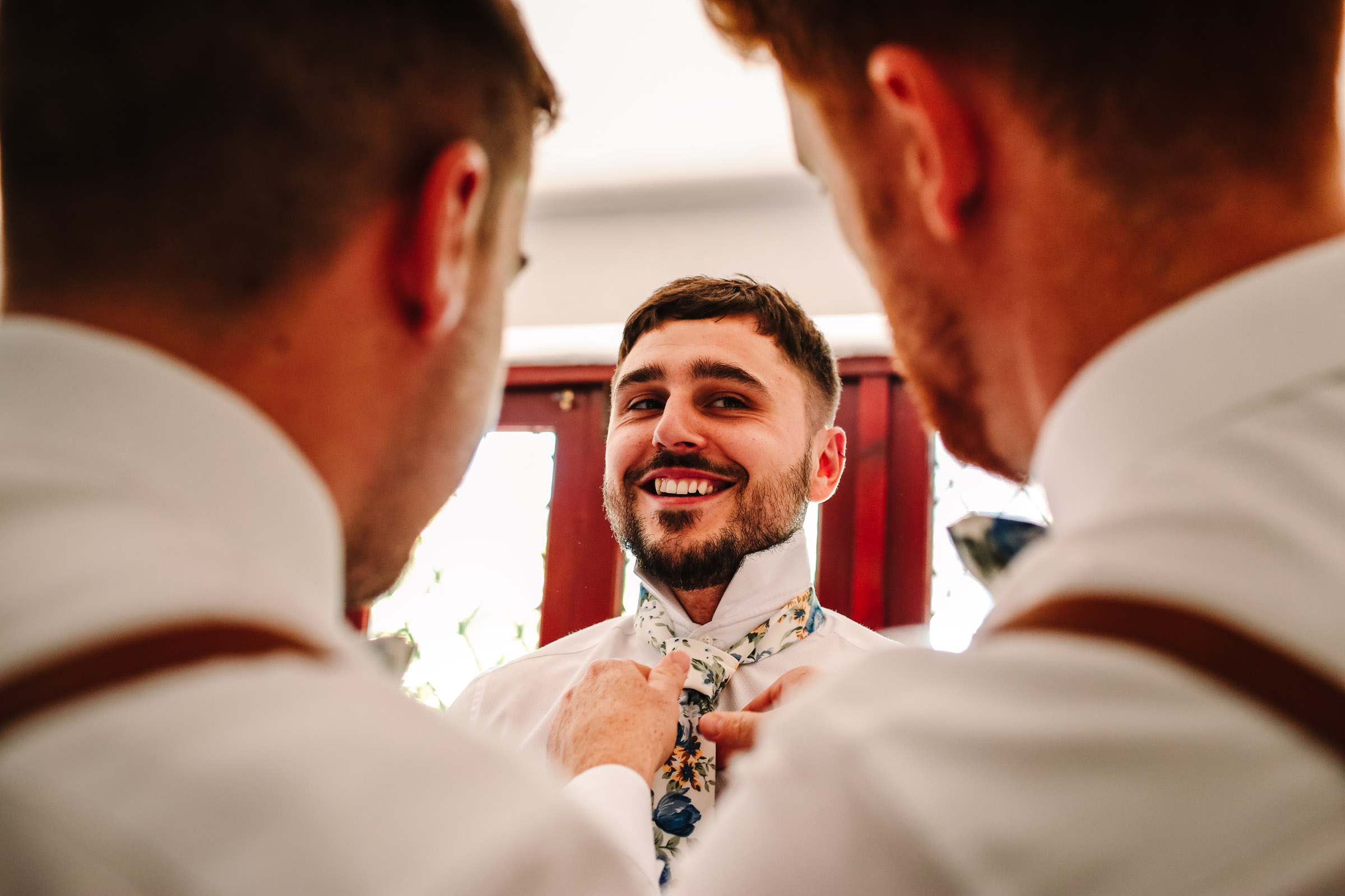 best man doing up grooms tie