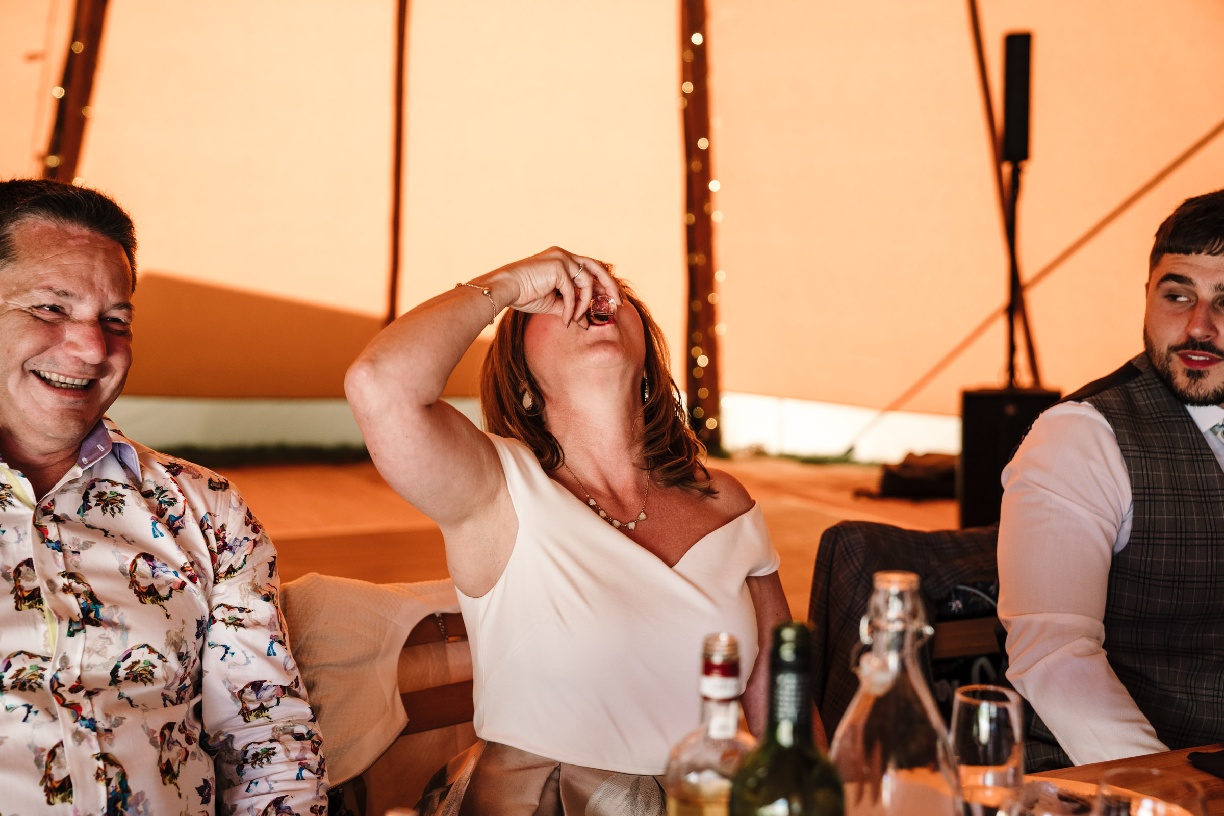 Mother of groom doing a shot at tipi wedding
