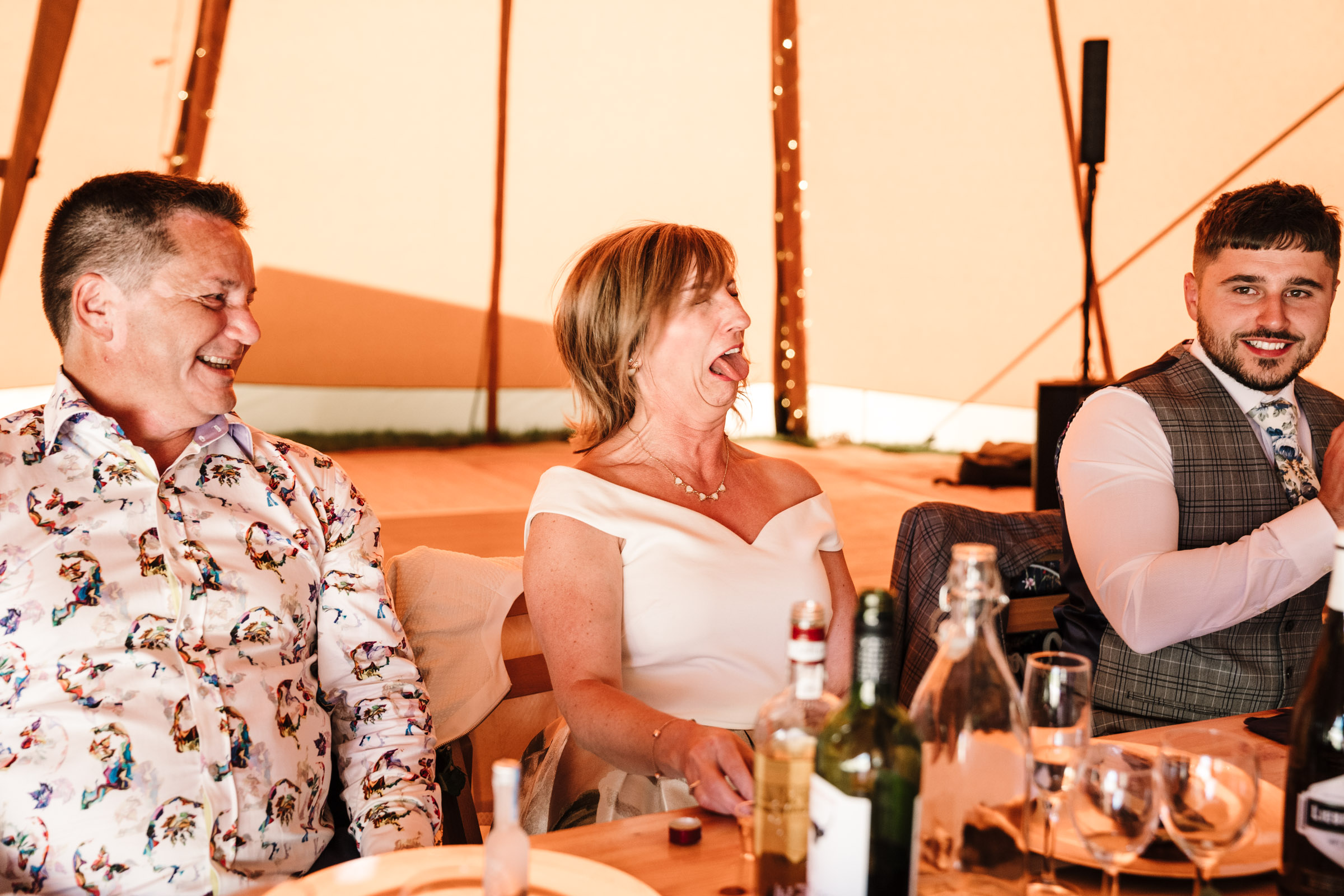 Mother of the bride pulling a face after taking a shot. Tipi wedding in Kenilworth