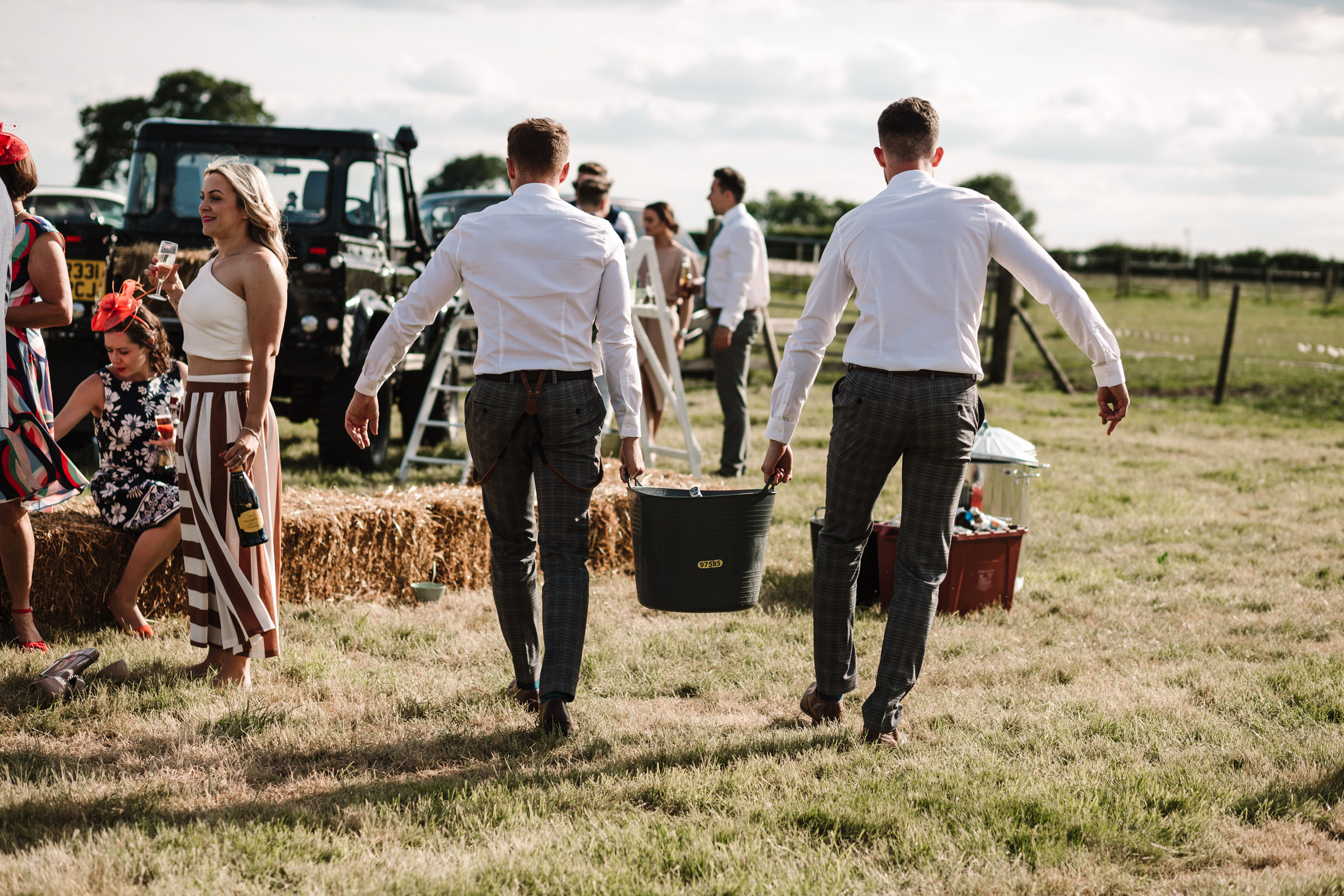 men carrying a bucket of beers, outdoor tipi wedding