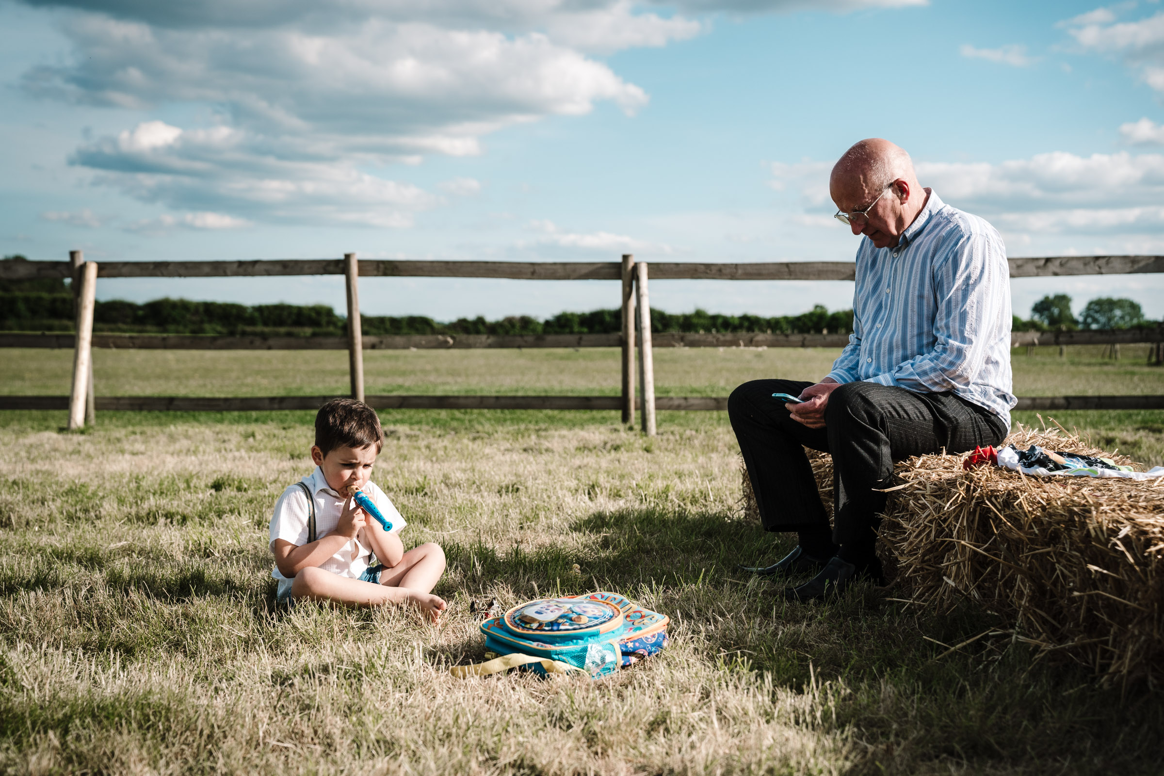 Man and boy sitting outside on a hay bale at a wedding