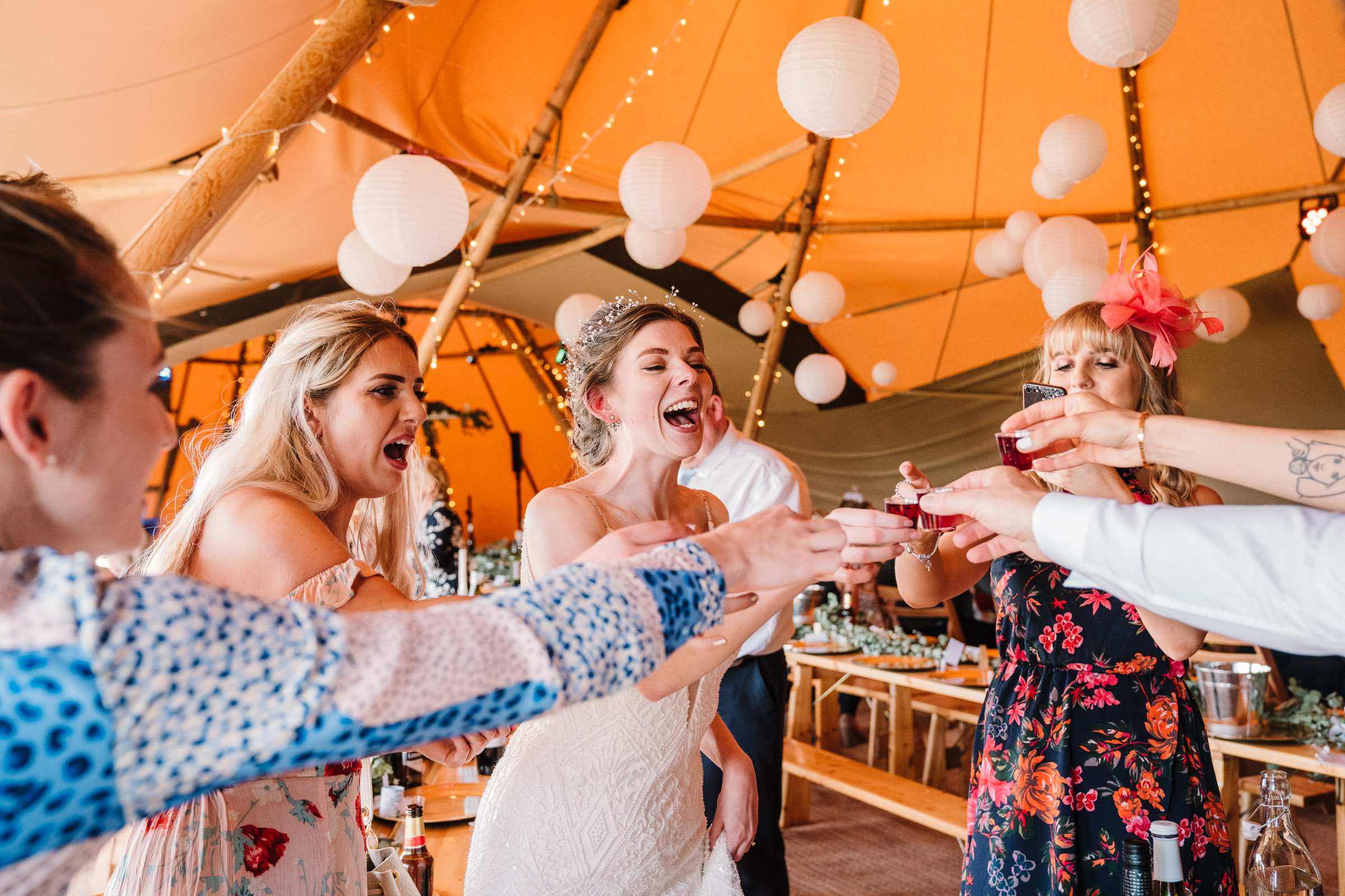 bride and guests drinking shots, tipi wedding