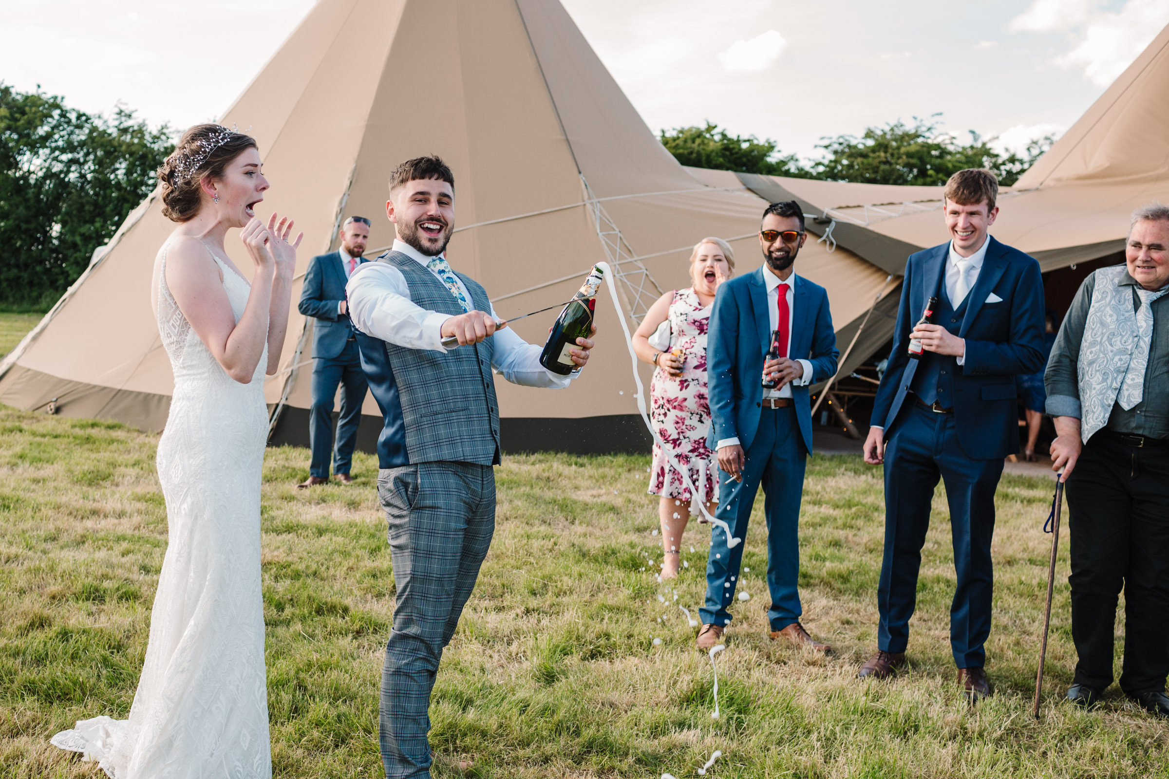Groom slicing off the top of champagne bottle with knife at outdoor tipi wedding