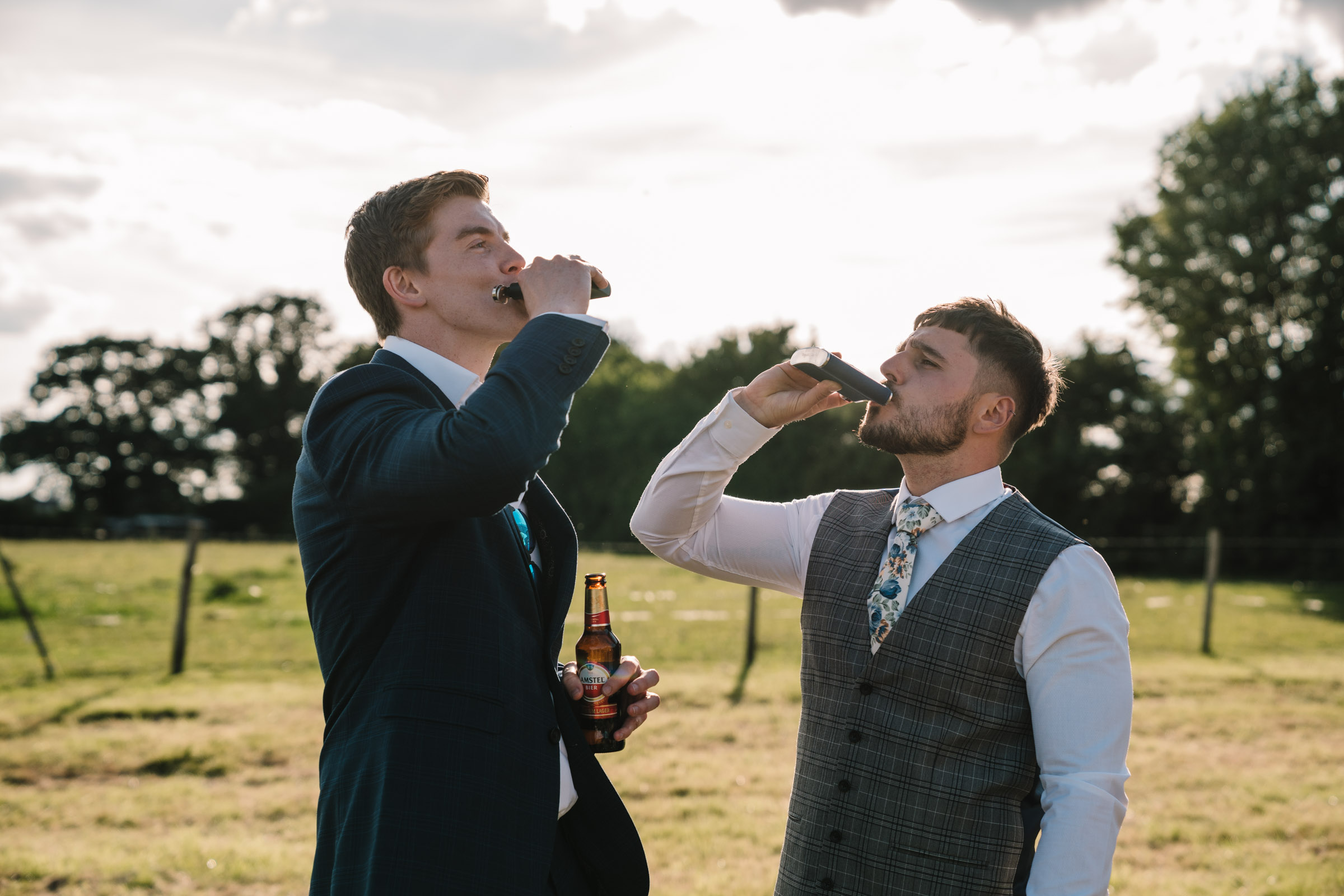 groom and friend drinking from a hip flask