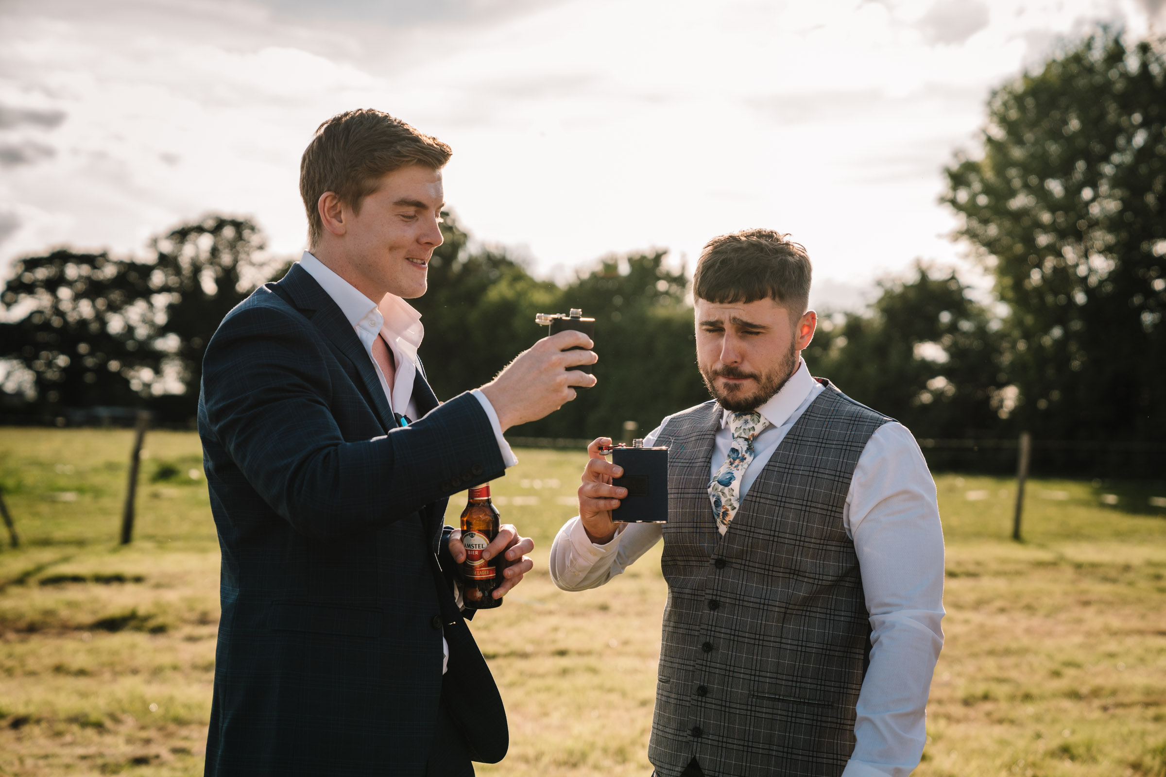 Groom pulling a face after having a drink from a hipflask