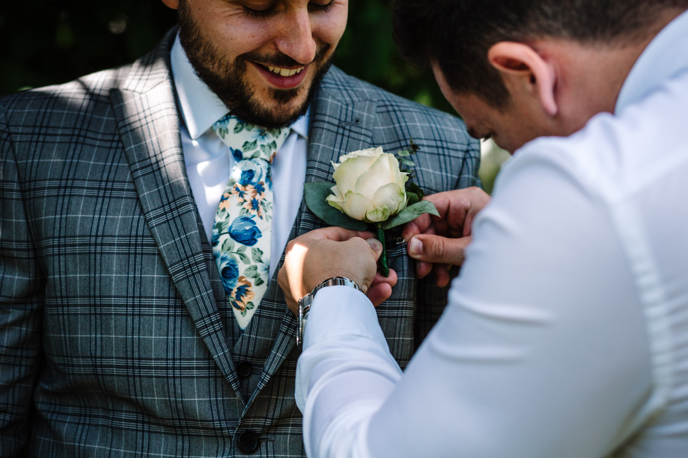 best man attaching grooms buttonhole