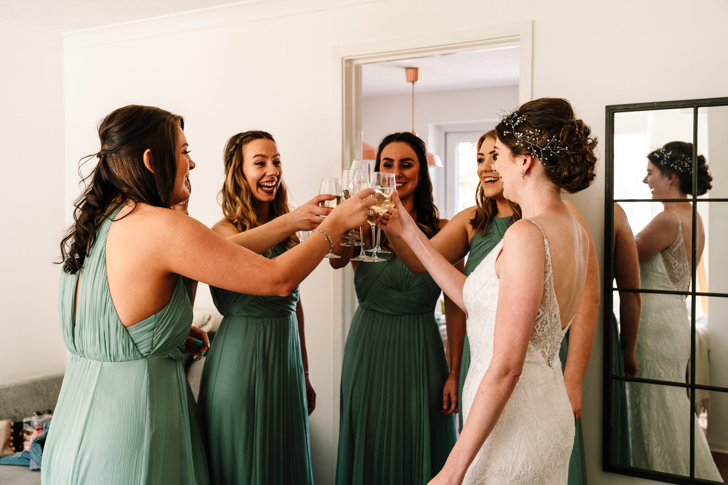 bride and bridesmaids clinking champagne glasses
