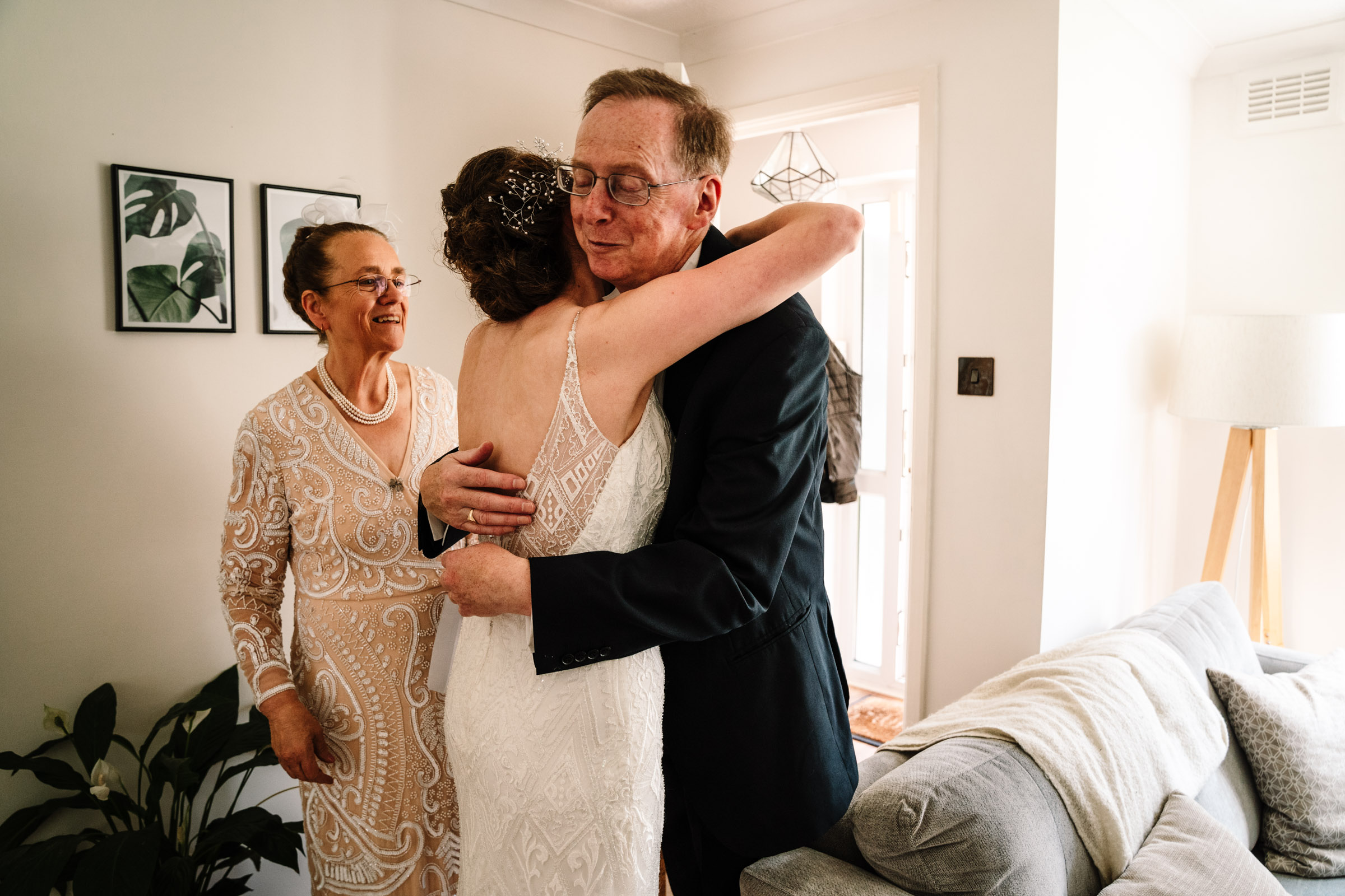 bride hugging her dad before they leave for her wedding