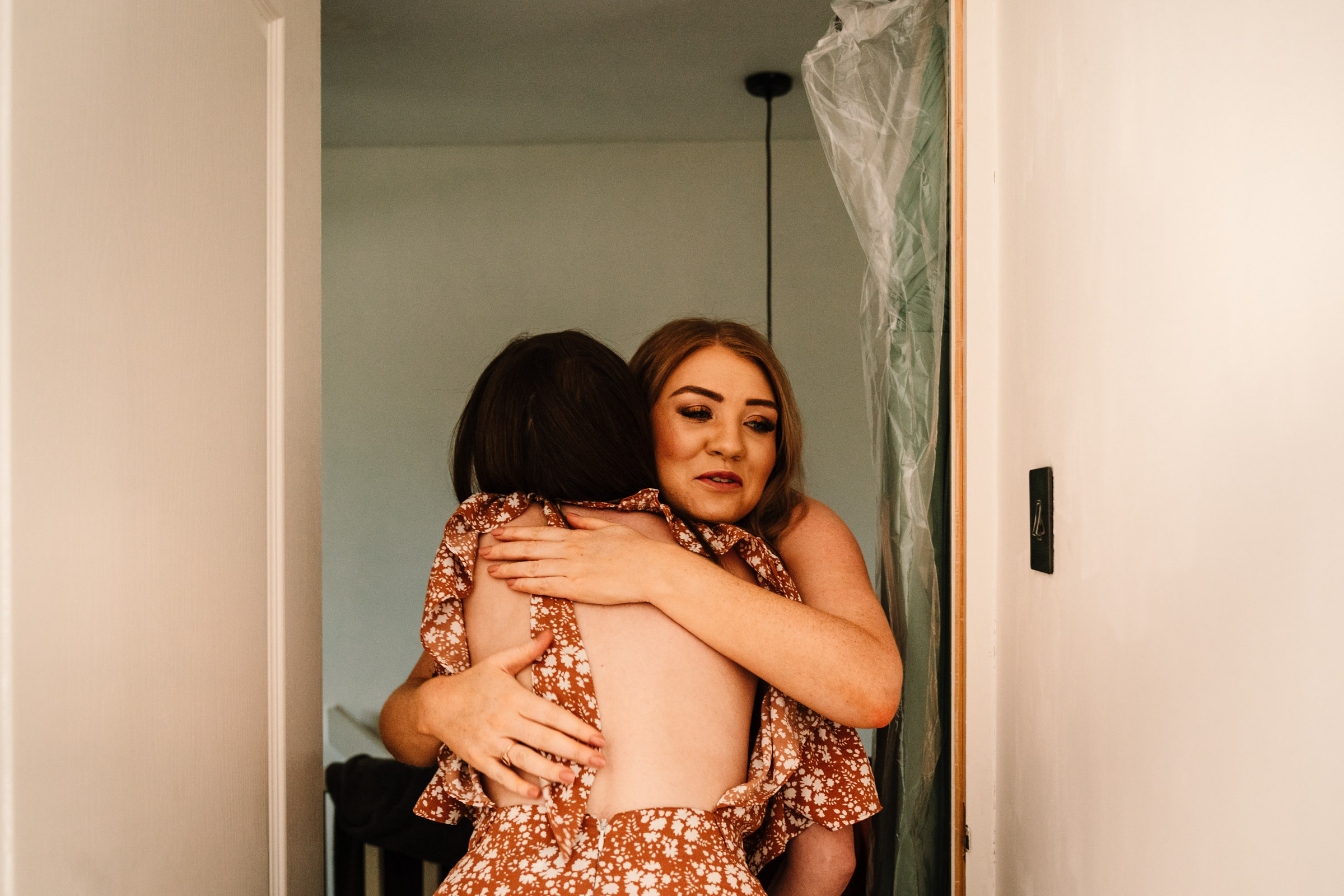 bridesmaid and bride hugging during bridal prep