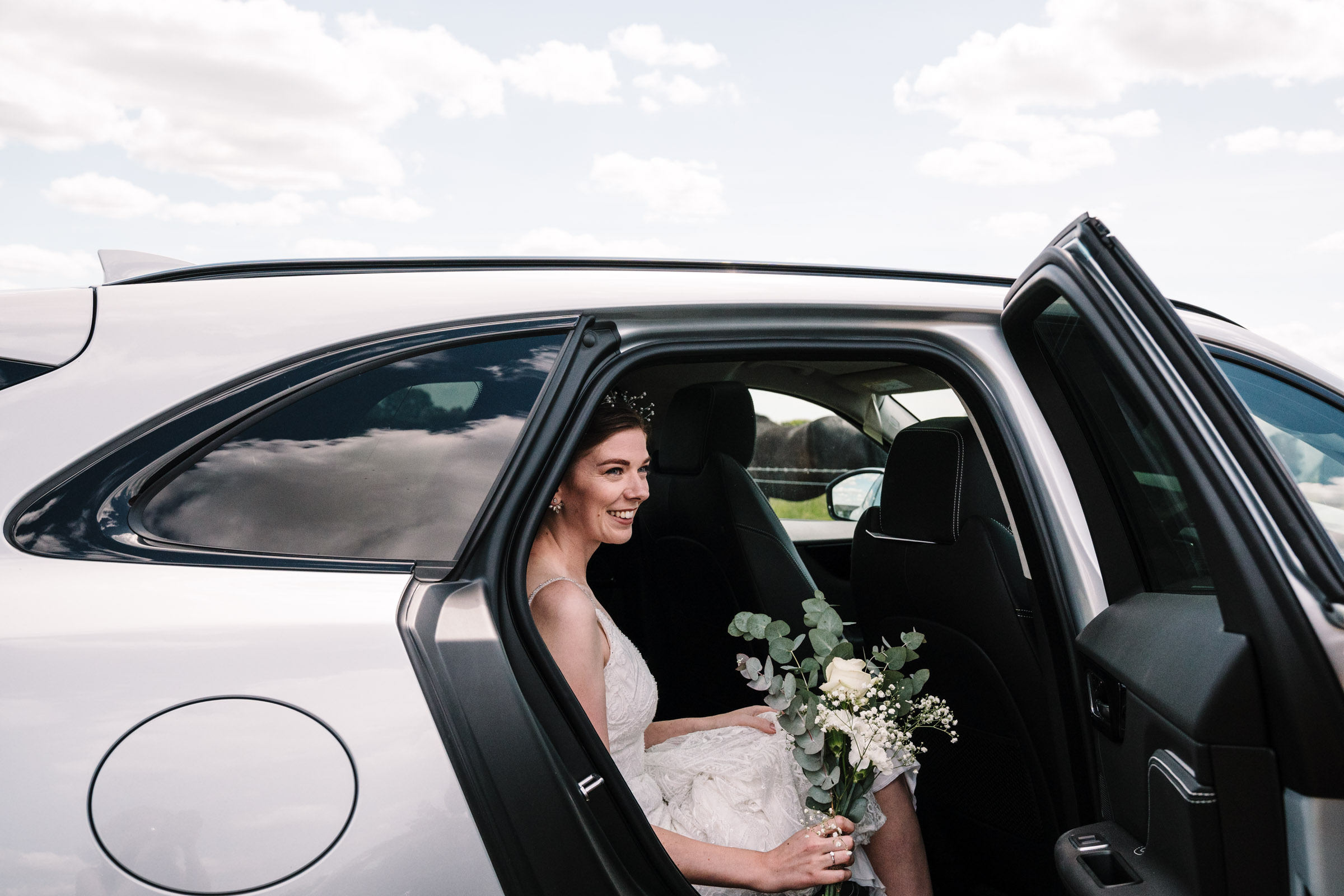 bride arriving at her wedding, getting out of the wedding car