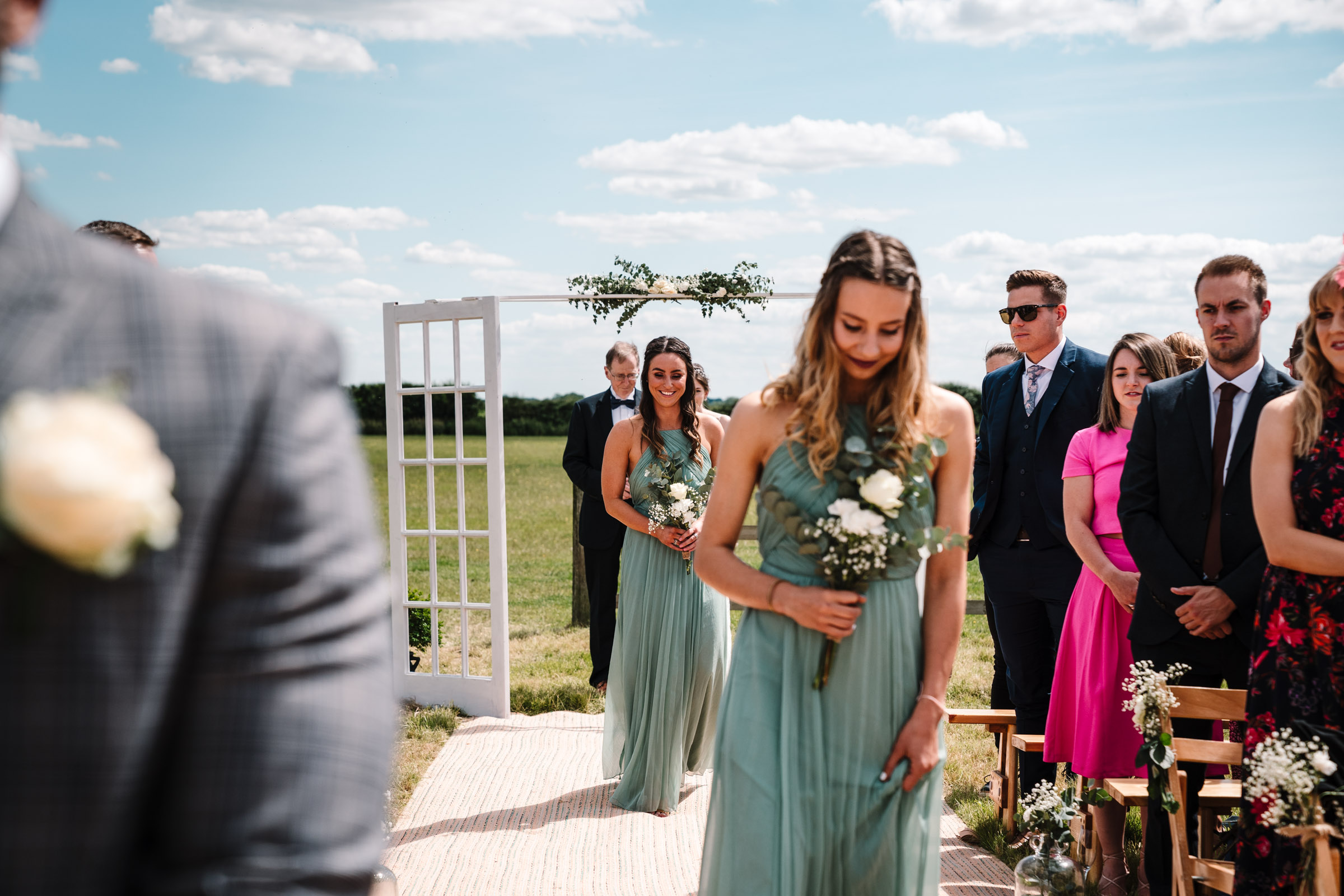 bridesmaids walking down the aisle at outdoor wedding, kenilworth