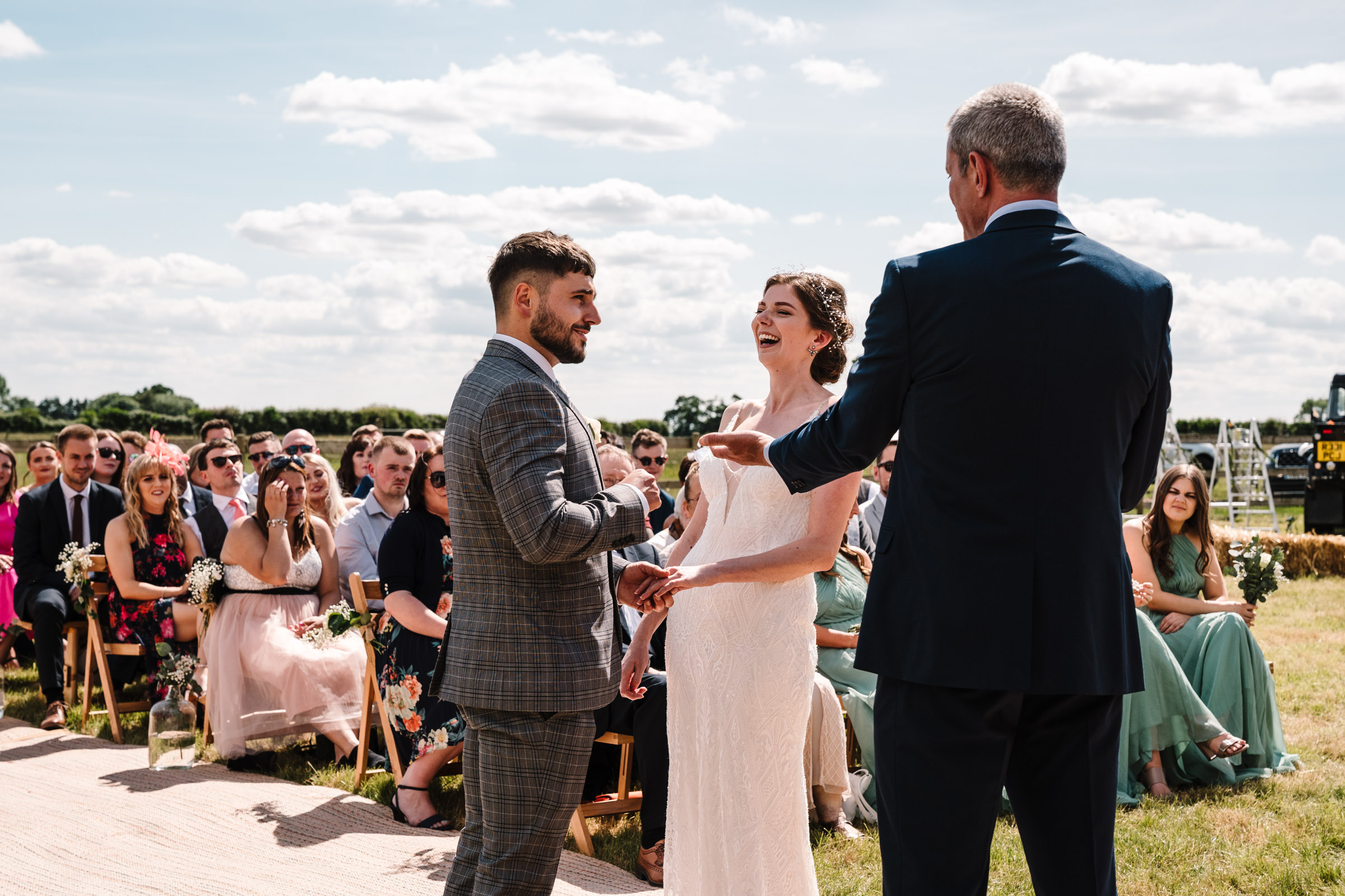 bride and groom laughing as they exchange rings at outdoor wedding ceremony
