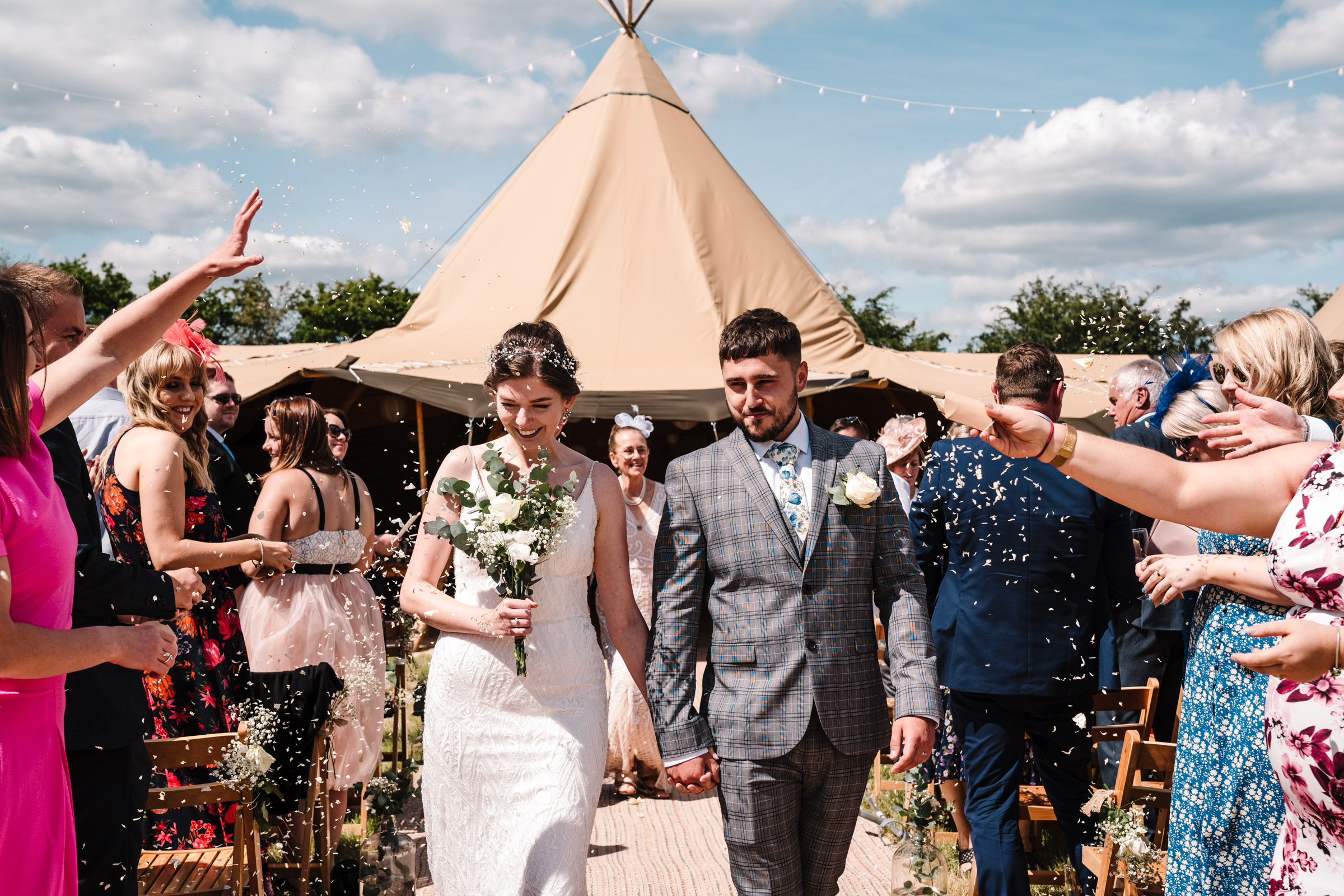 guests throwing confetti over the bride and groom at tipi wedding, kenilworth