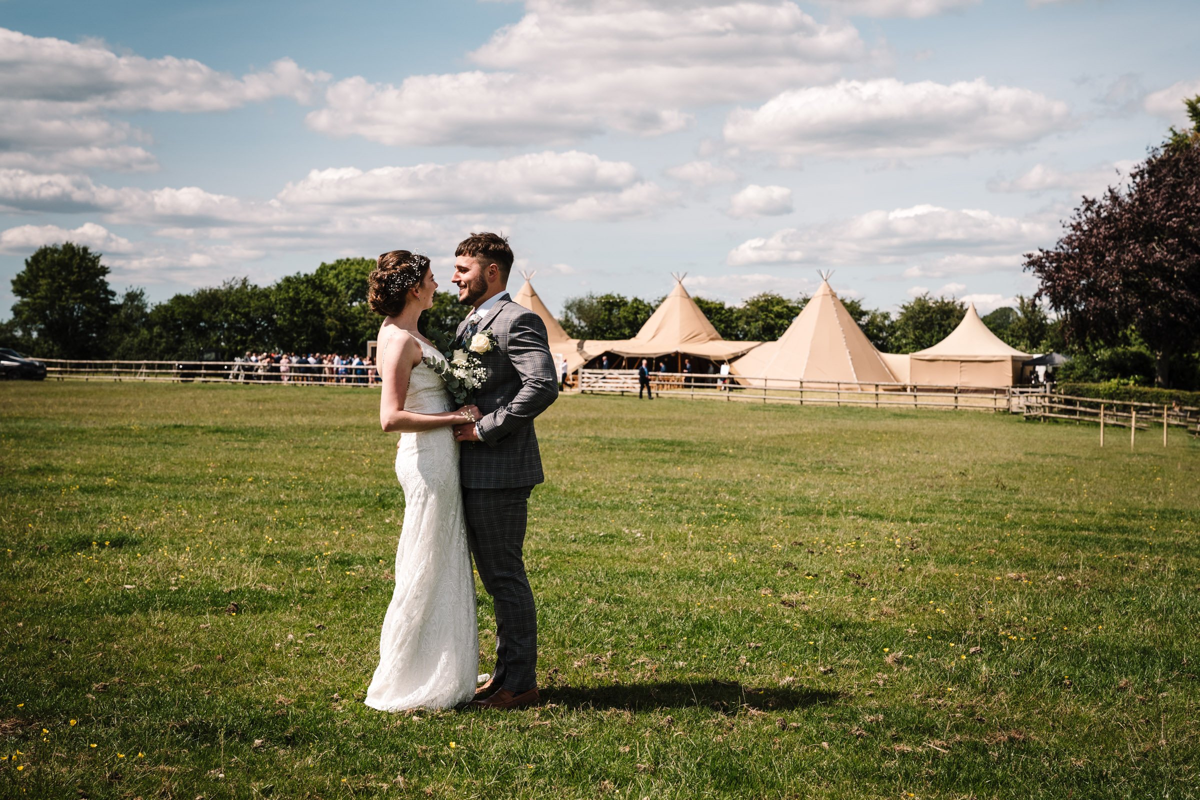 bride and groom standing in front of tipis at outdoor wedding