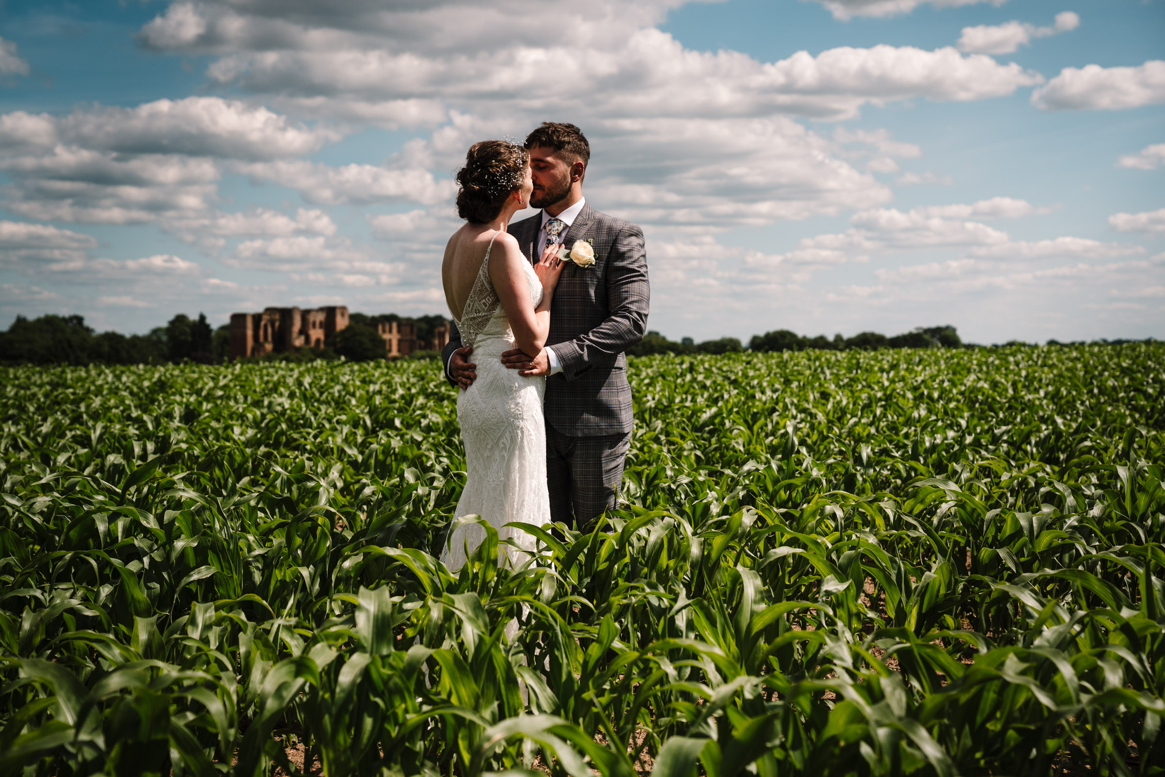 bride and groom kissing in a field in front of kenilworth castle