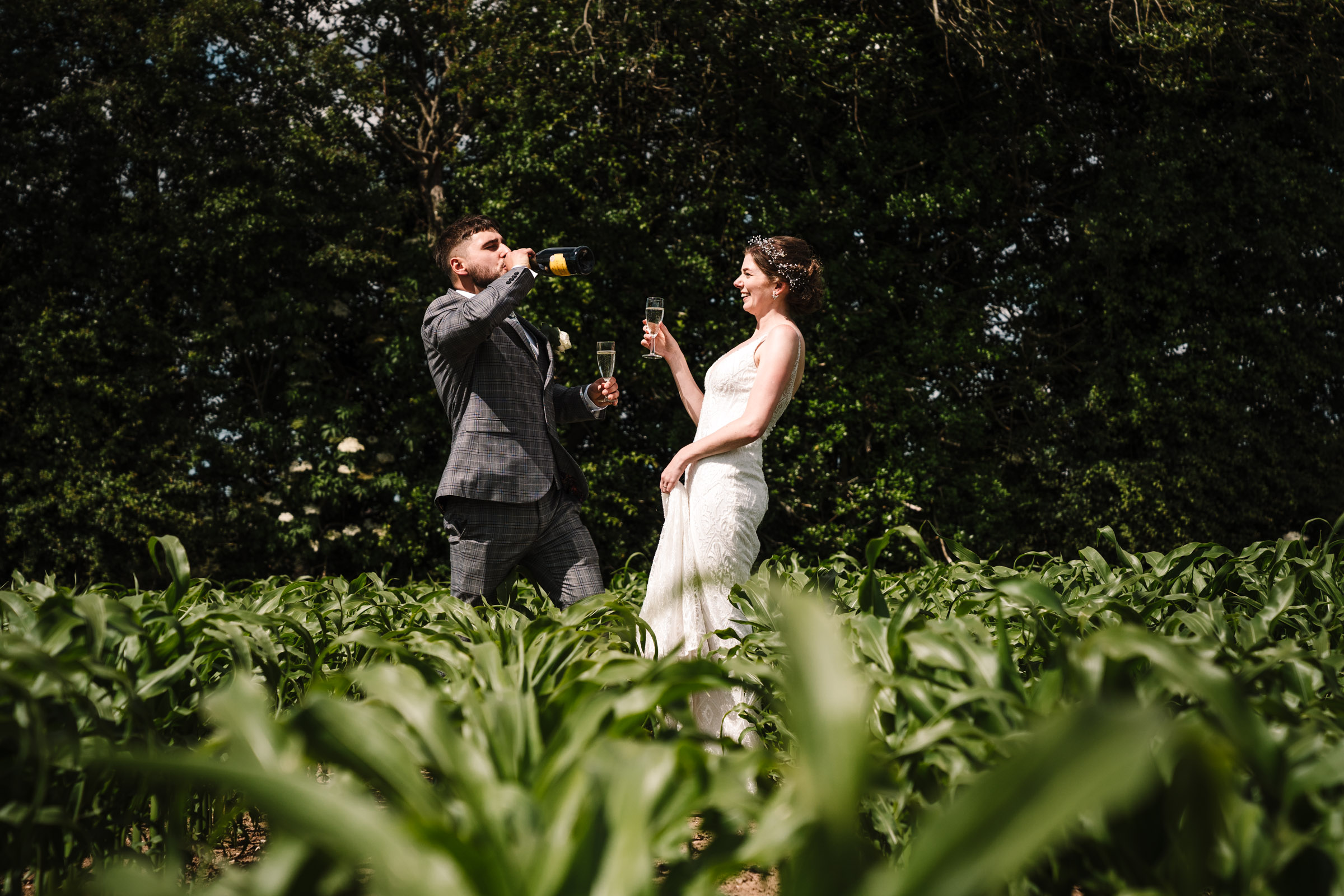 bride and groom drinking champagne in a field