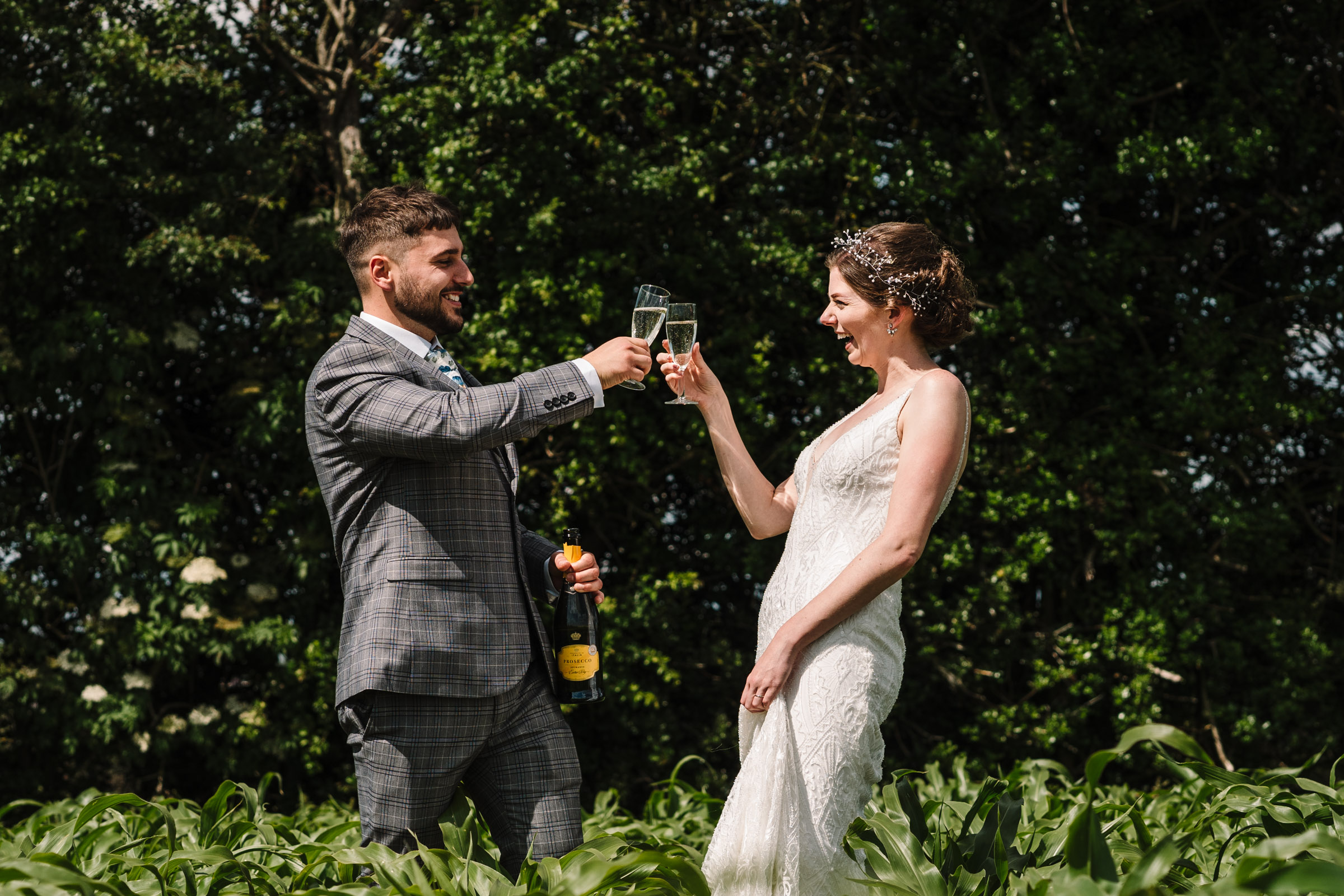 bride and groom, just married, clinking champagne glasses in field