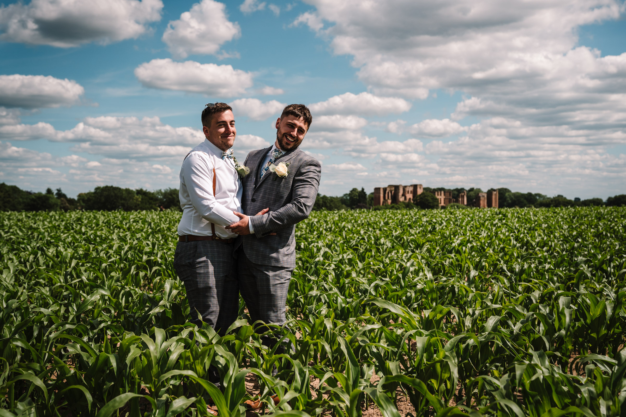 Groom and best man hugging in a field in front of kenilworth castle