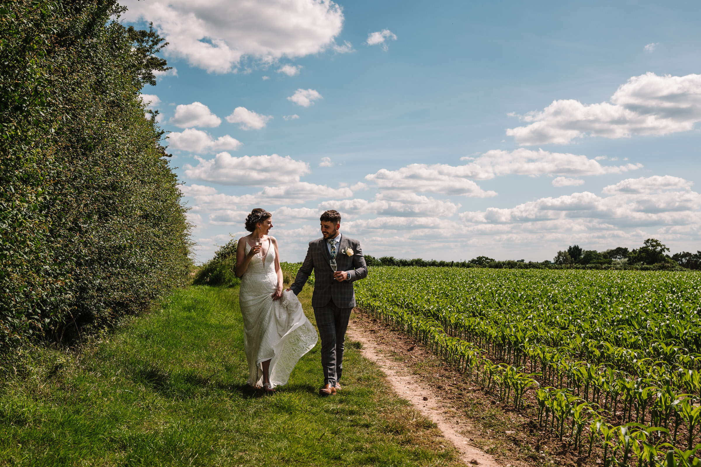 bride and groom walking down field in Kenilworth, holding champagne