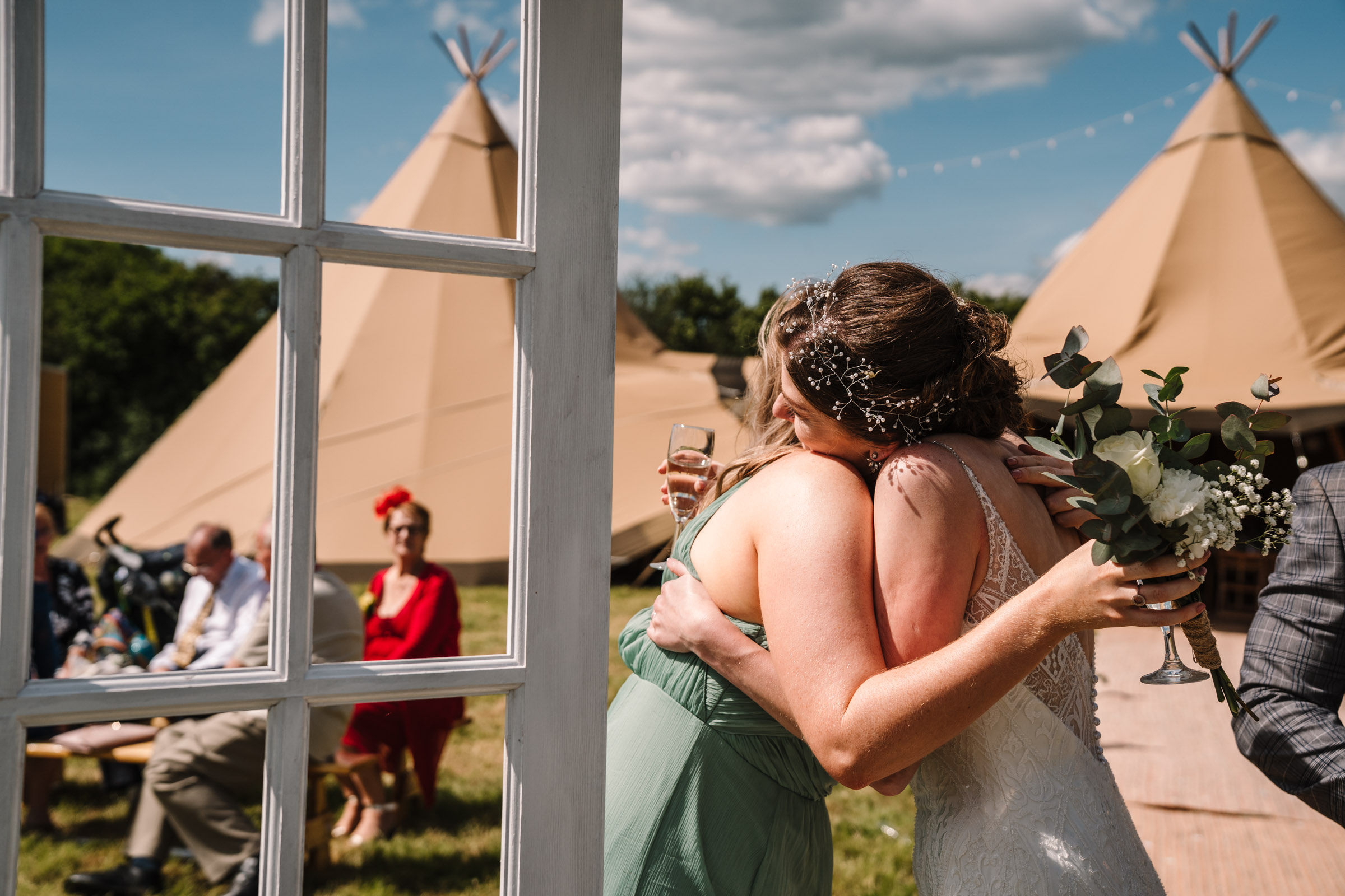 bridesmaid hugging bride, outdoor wedding, kenilworth