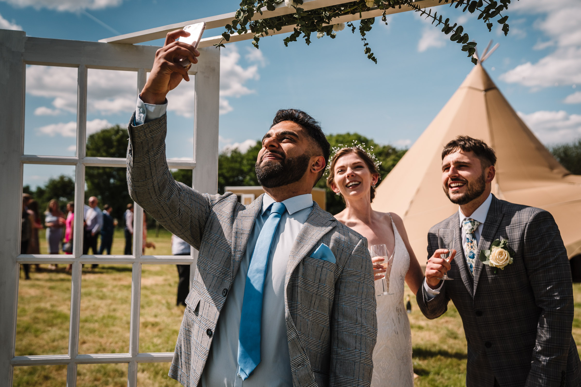guest taking a selfie with bride and groom, outdoor wedding Kenilworth