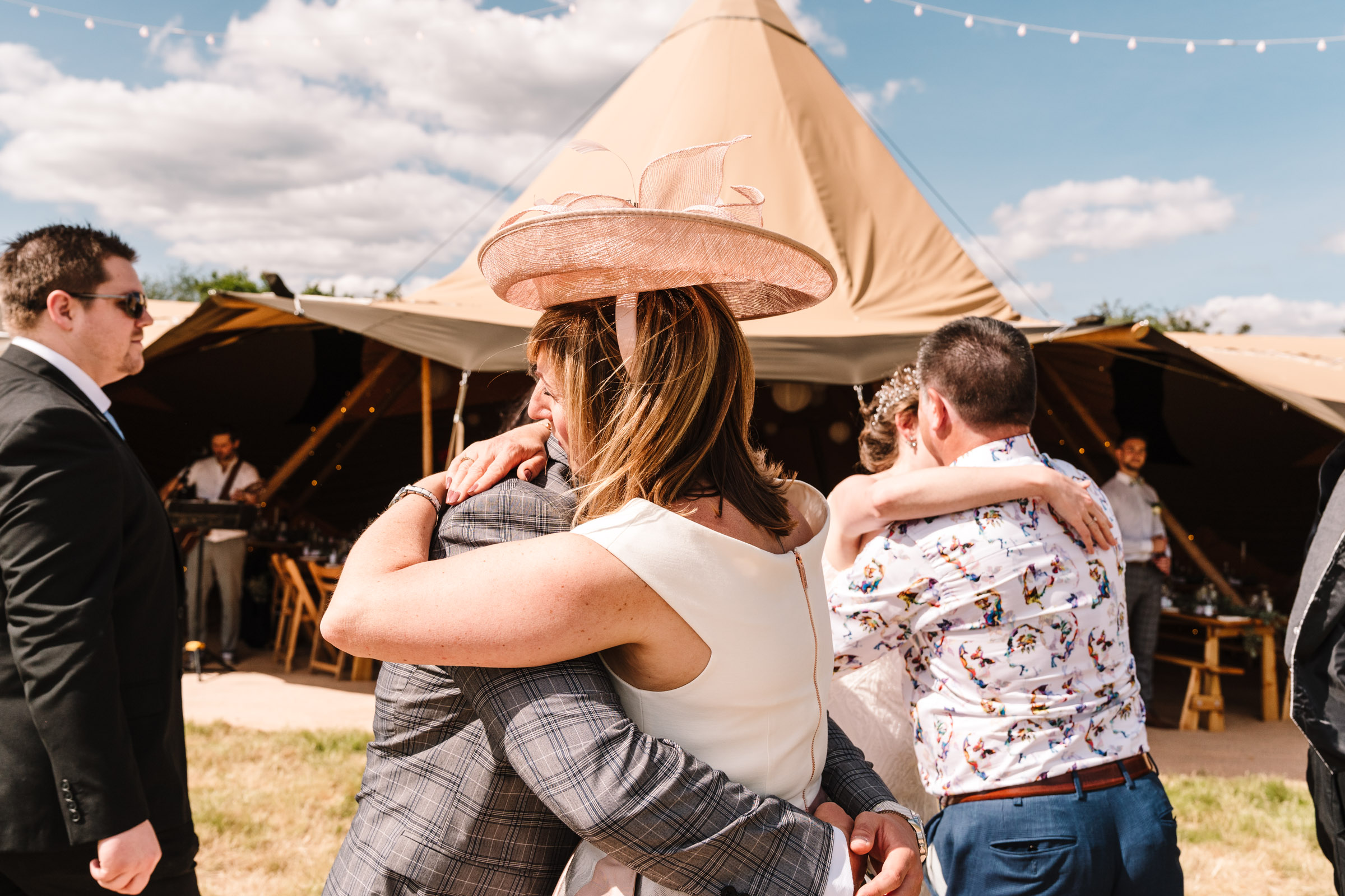 guests hugging bride and groom, tipi wedding