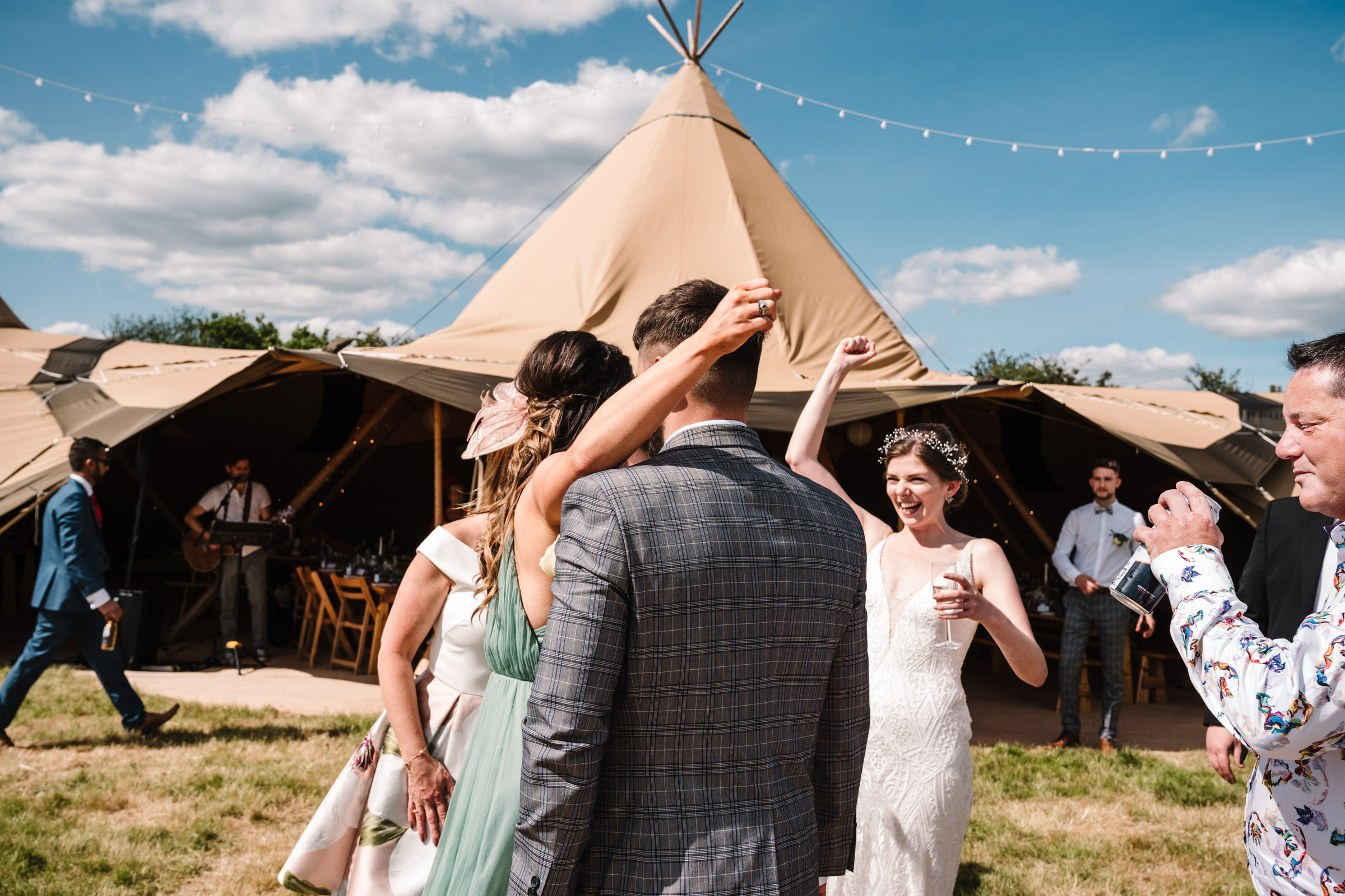 bride cheering with guest outside tipi at kenilworth wedding