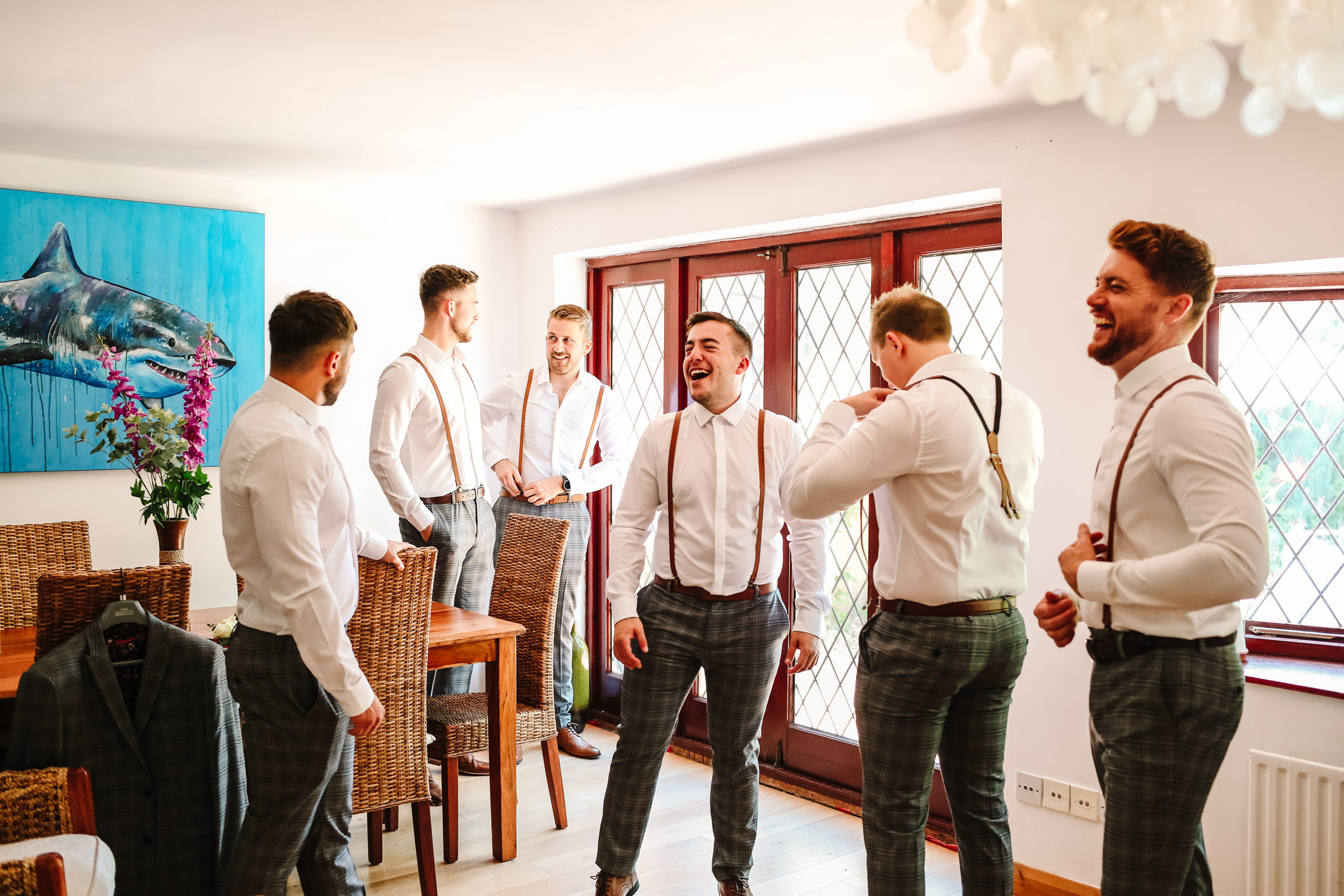 groomsmen laughing as they get dressed ready for wedding