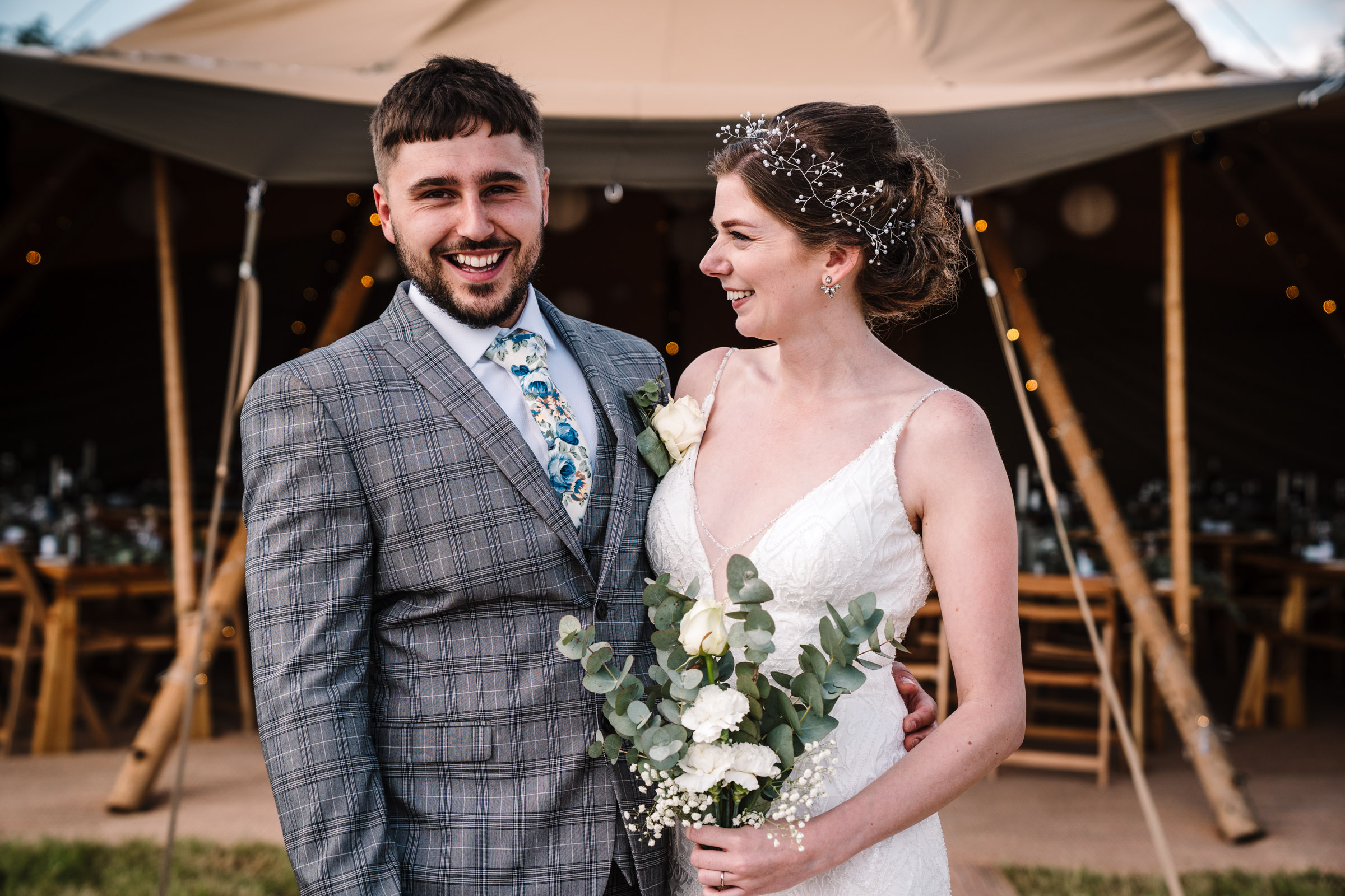 bride and groom standing in front of tipi at outdoor wedding