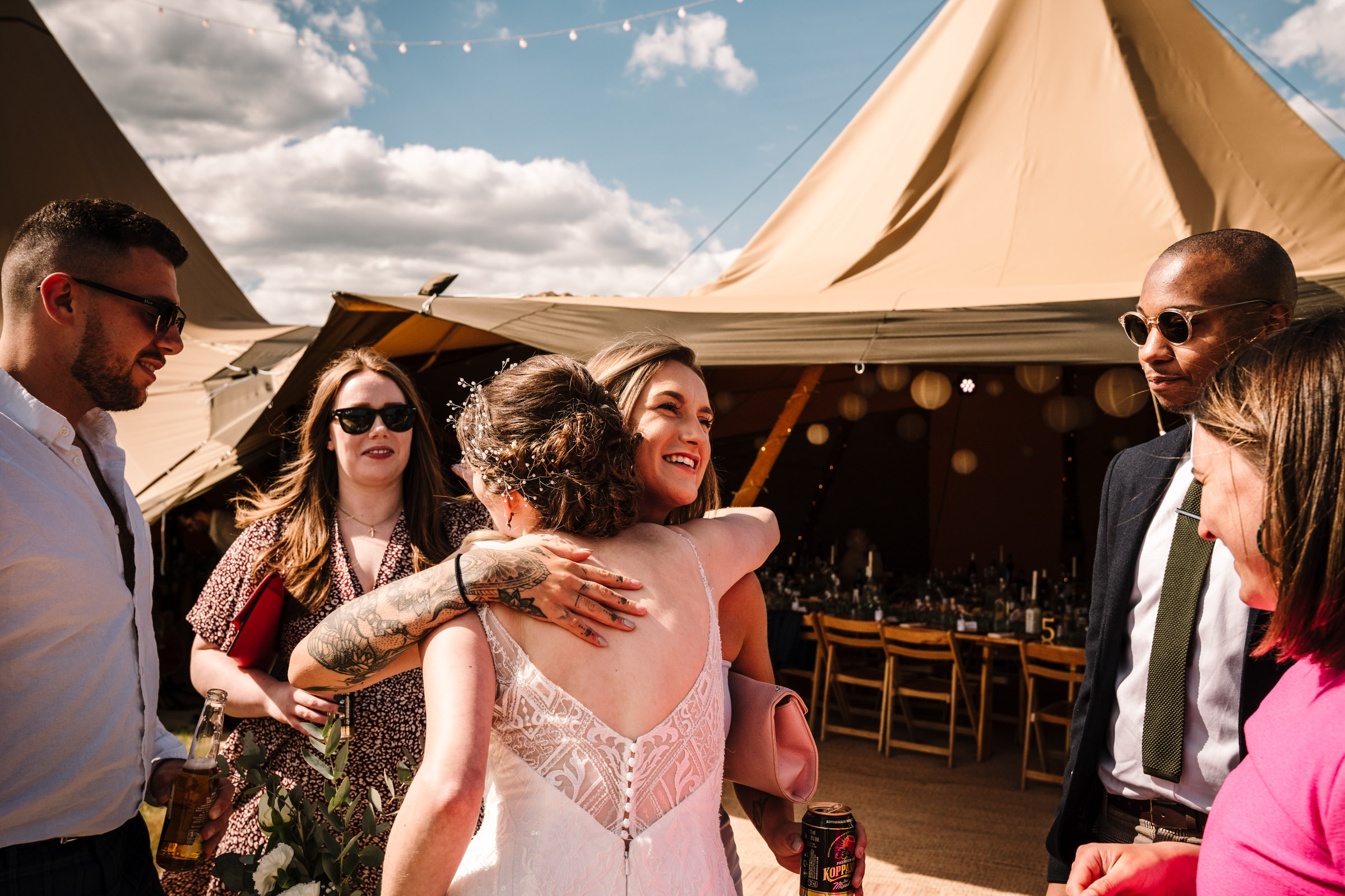 guest greeting bride at tipi wedding