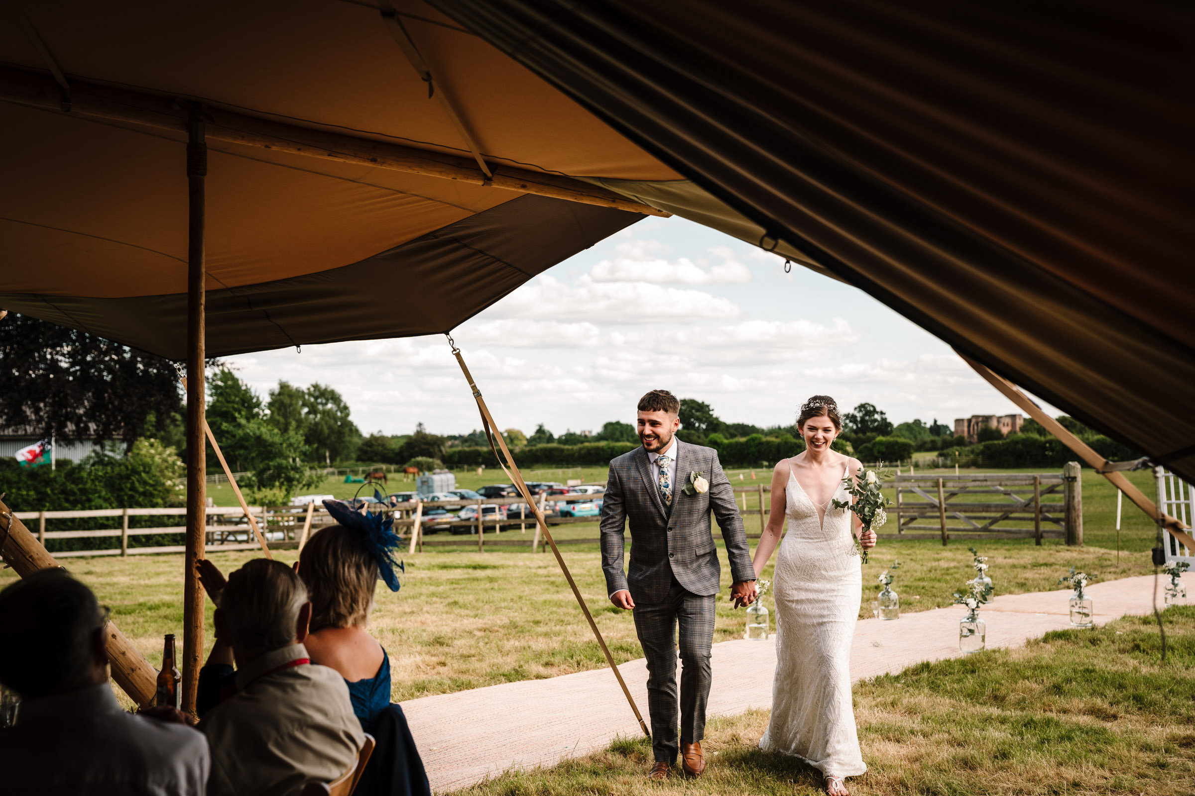 bride and groom entering tipi for wedding breakfast