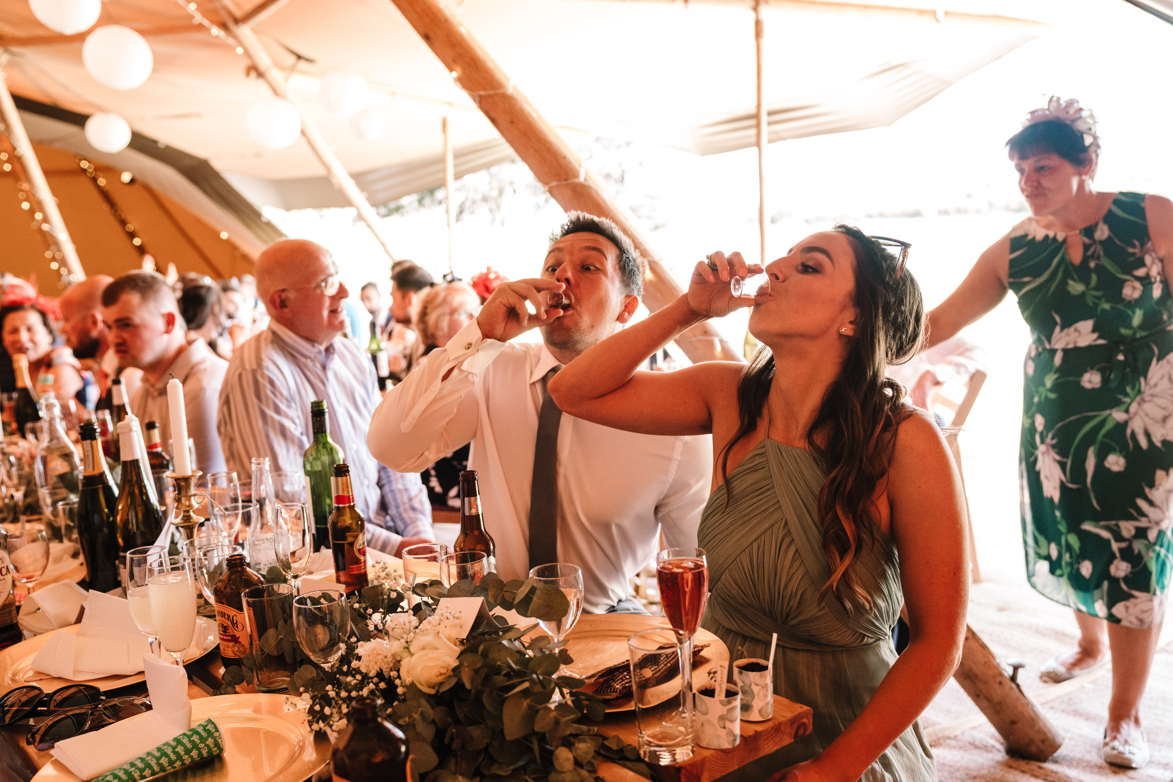 guests downing shots at tipi wedding