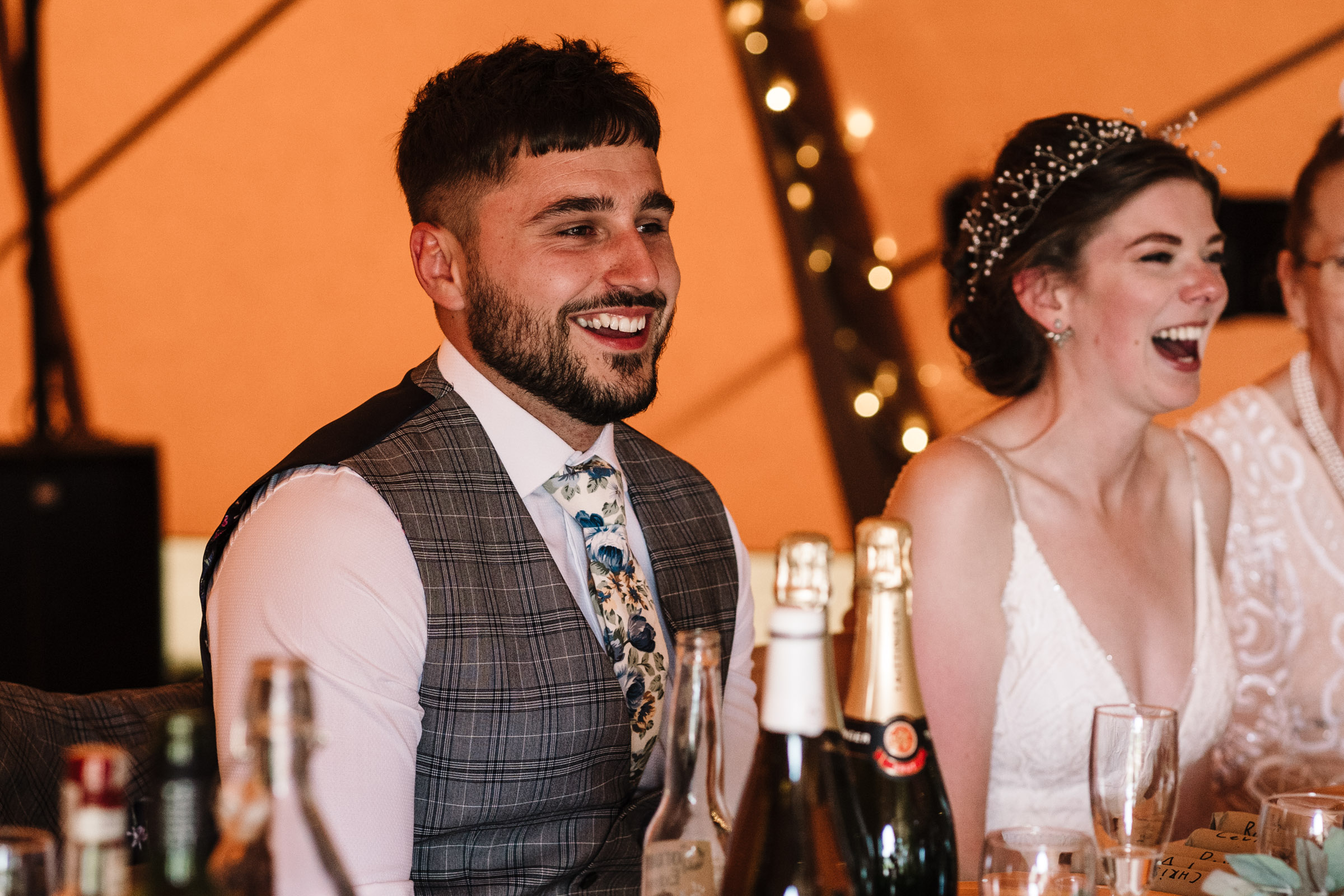 Groom and bride laughing at speeches, tipi wedding, kenilworth