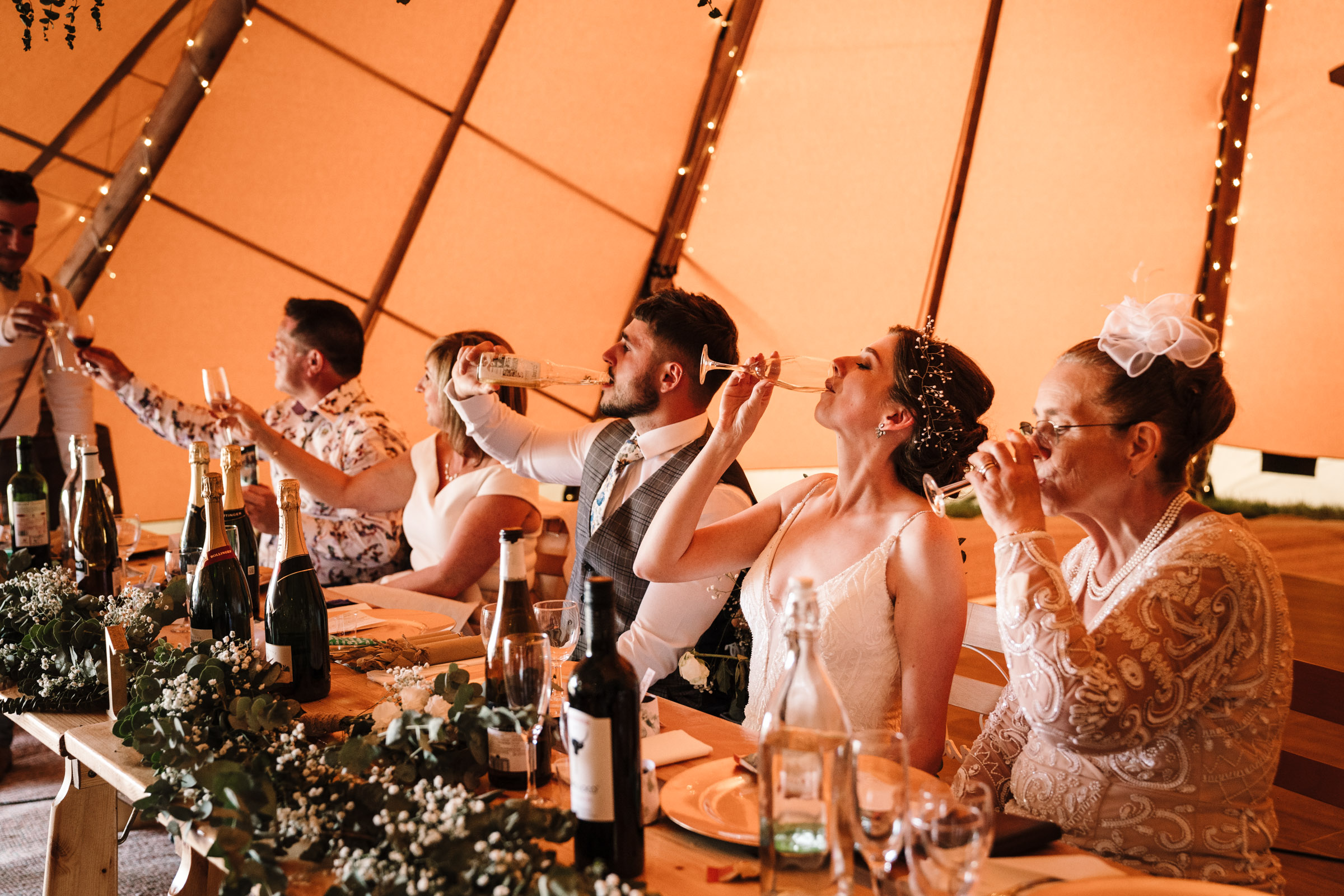 Top table at tipi wedding, bride and groom drinking champagne
