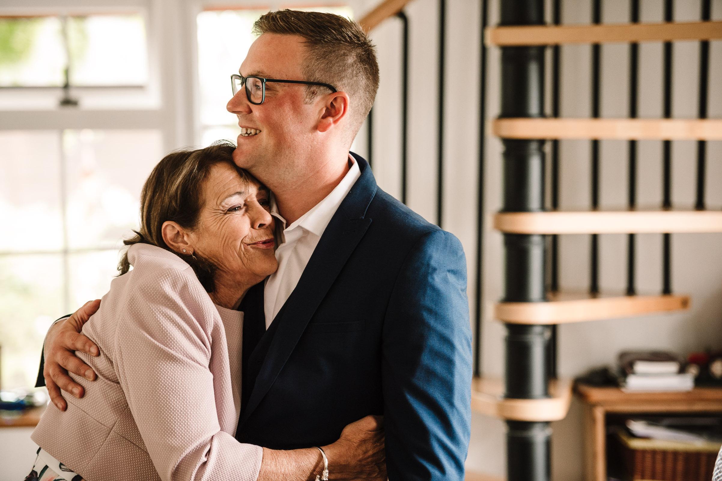 Mum hugging son on wedding morning