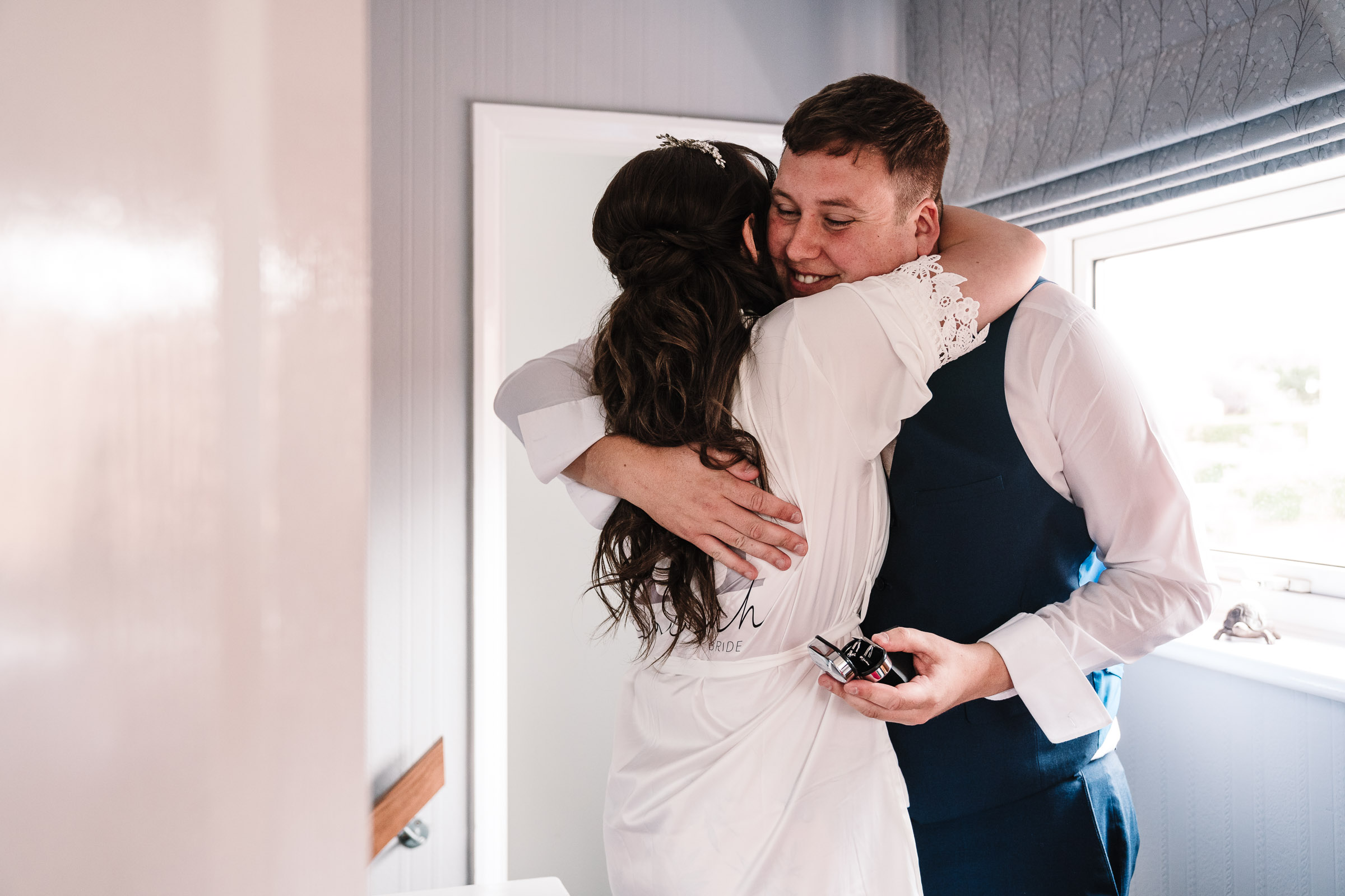 bride hugging brother after giving him a gift on wedding morning