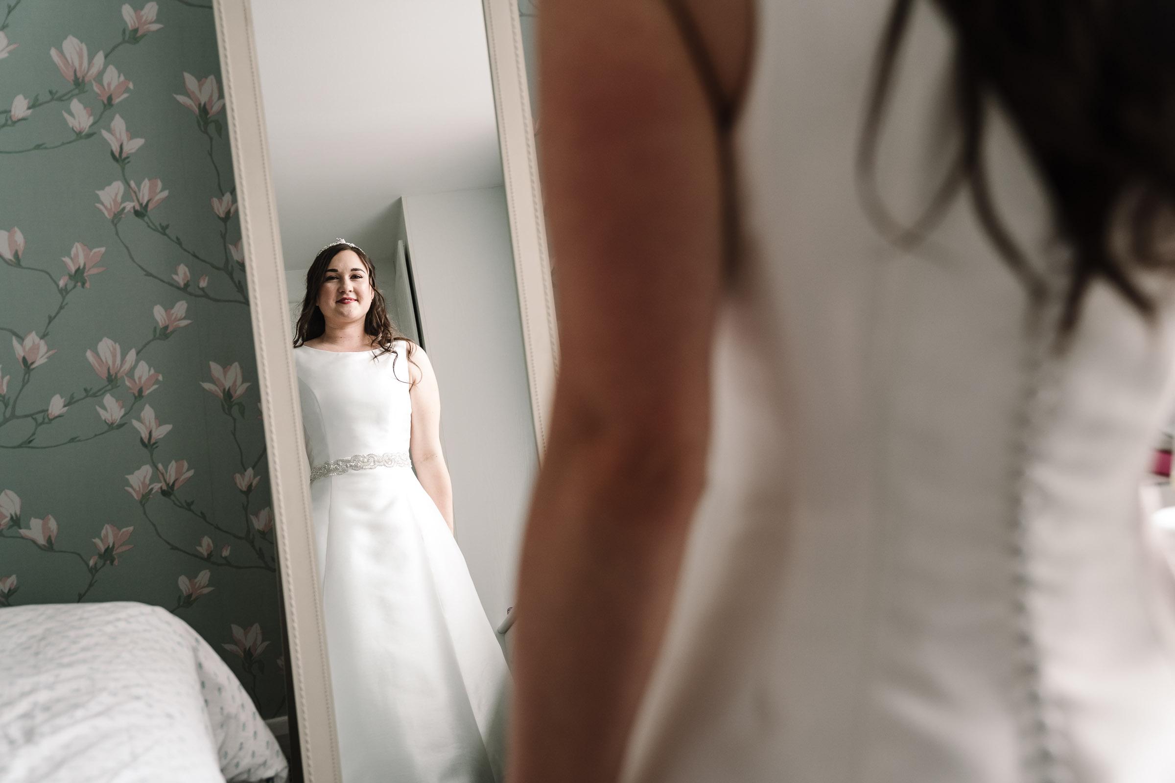 bride looking at herself in mirror in wedding dress
