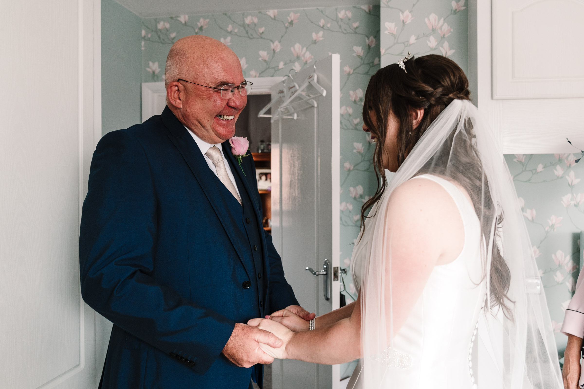 bride and her dad as he sees her in wedding dress