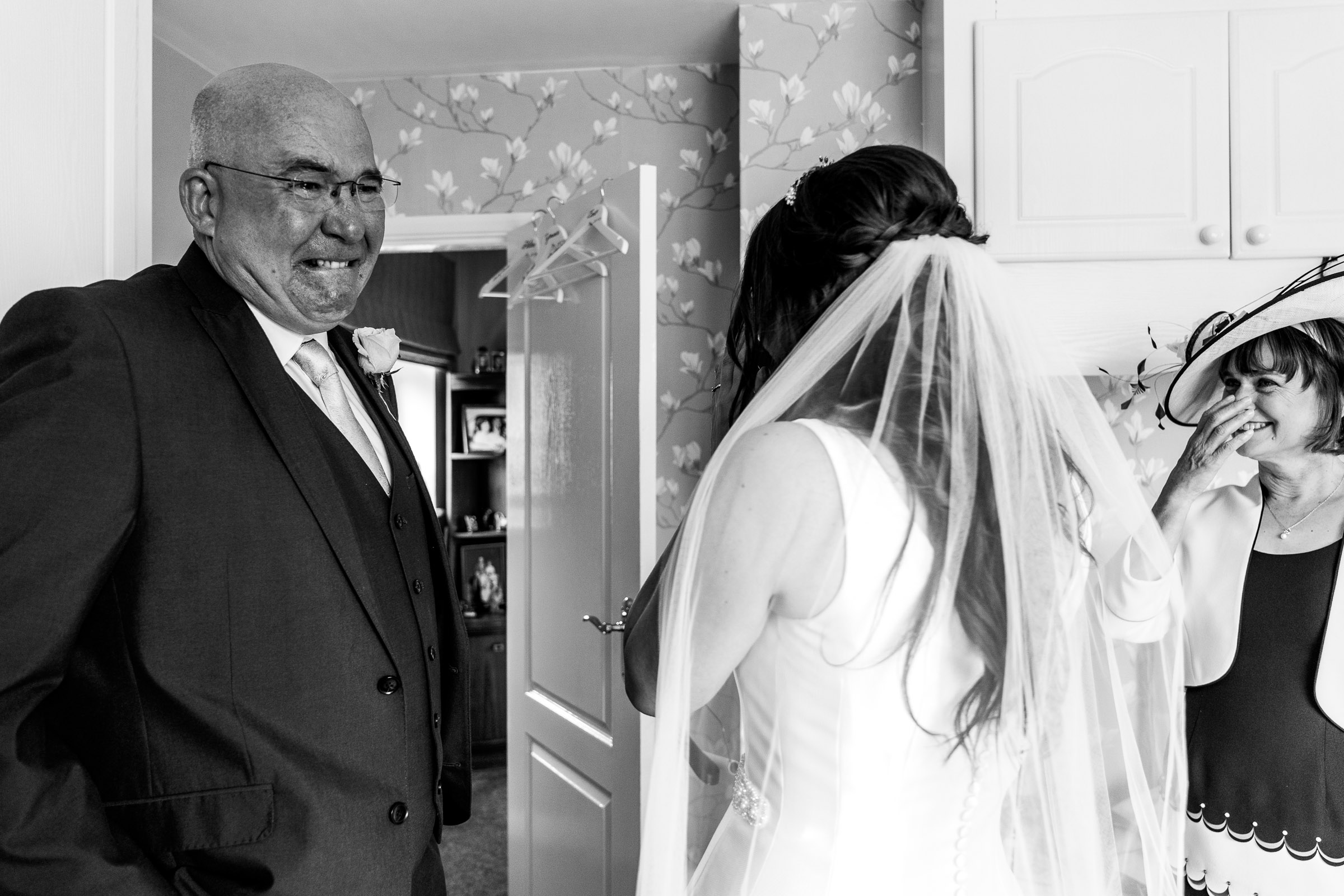 father of the bride crying as her sees his daughter in wedding dress
