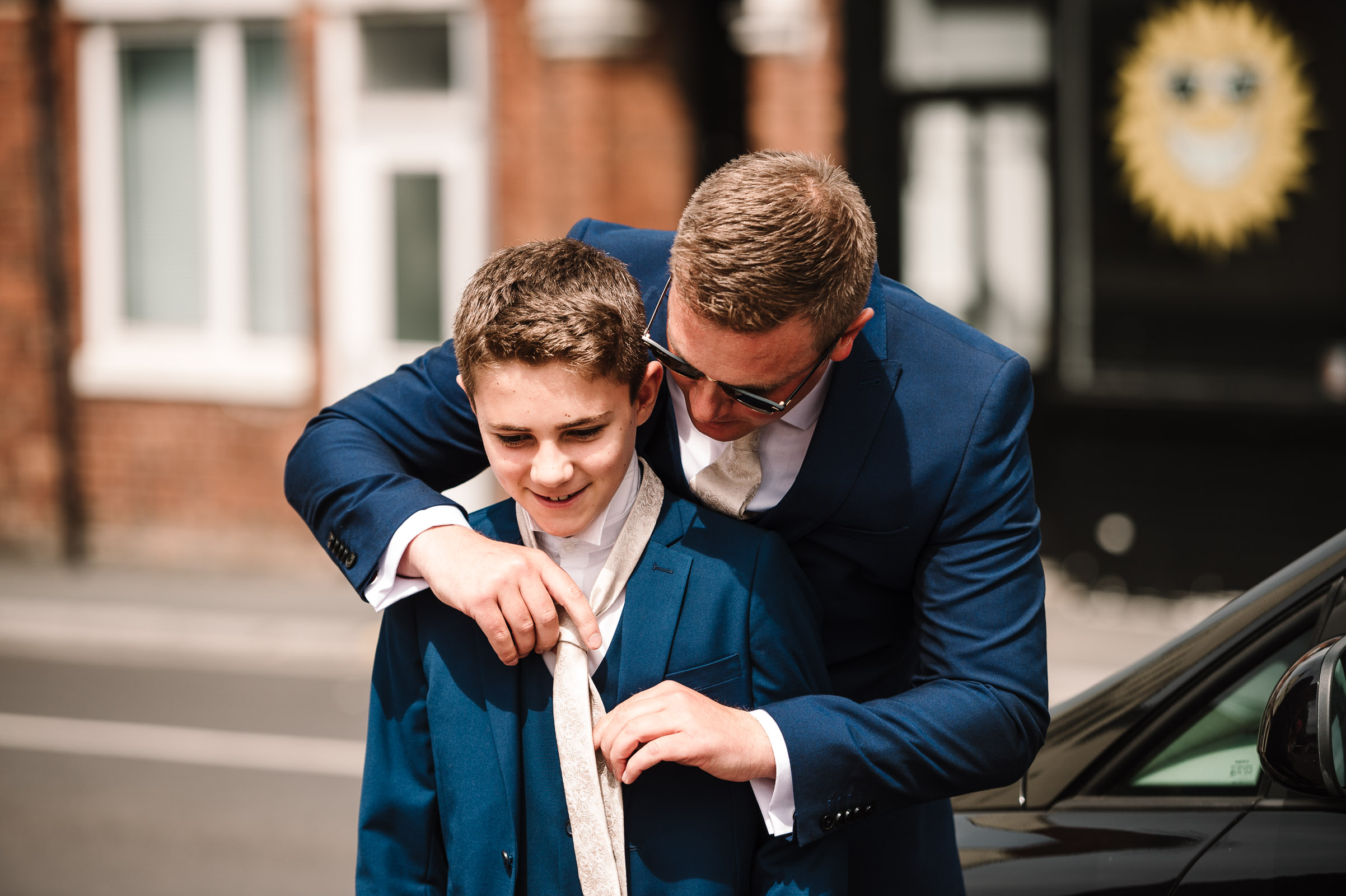 groom doing up tie on younger guest