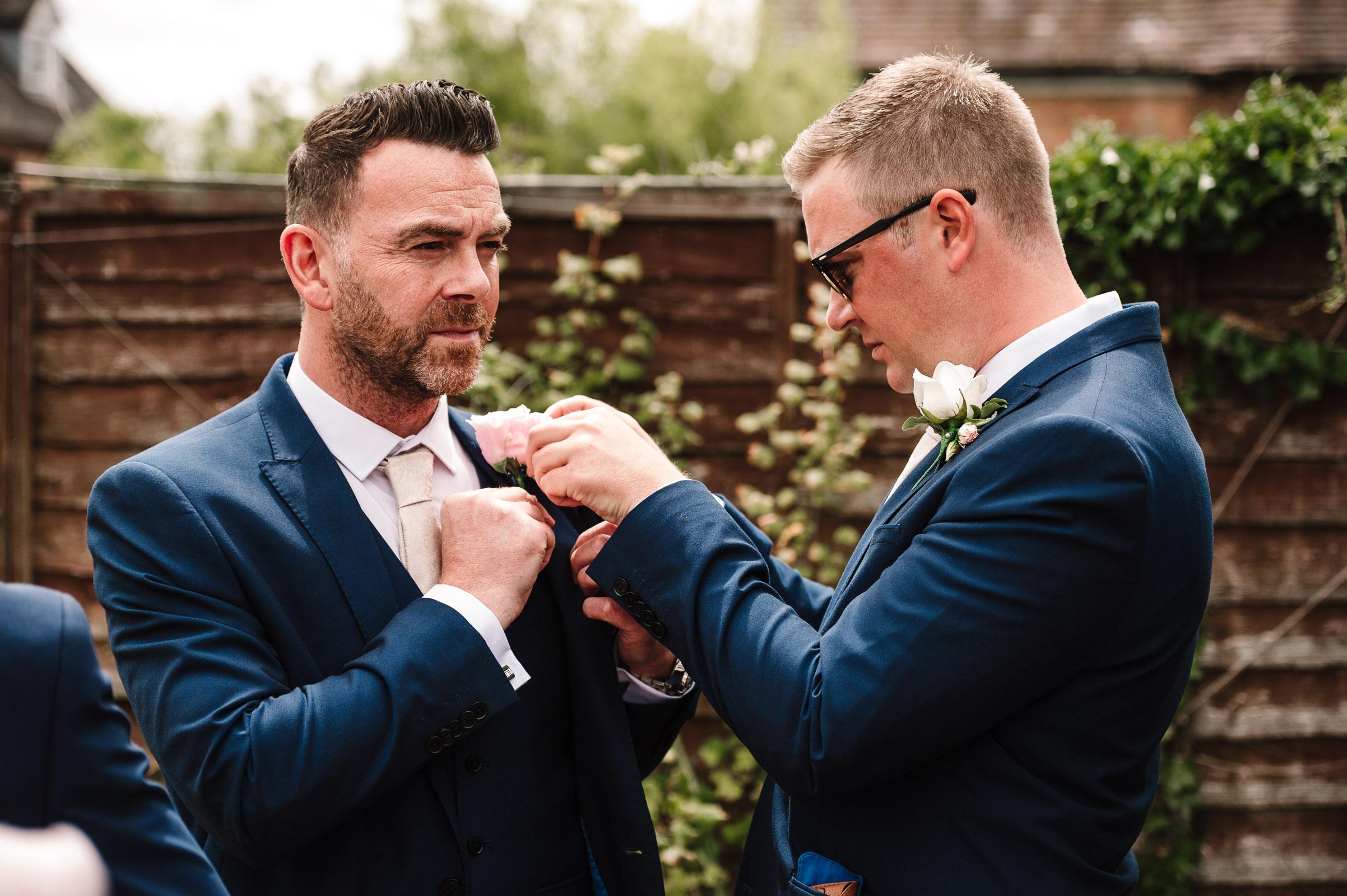 groom pinning button hole on groomsmen